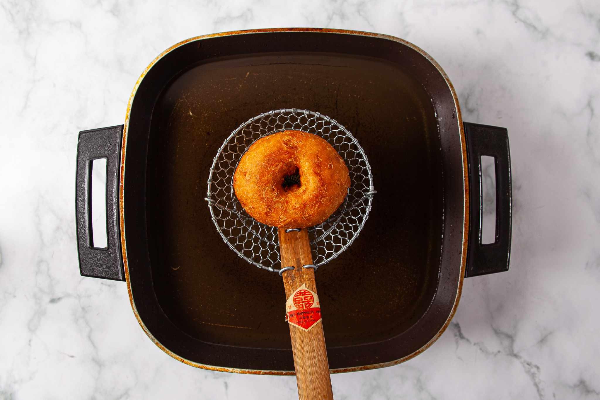 Fried doughnut draining over hot oil