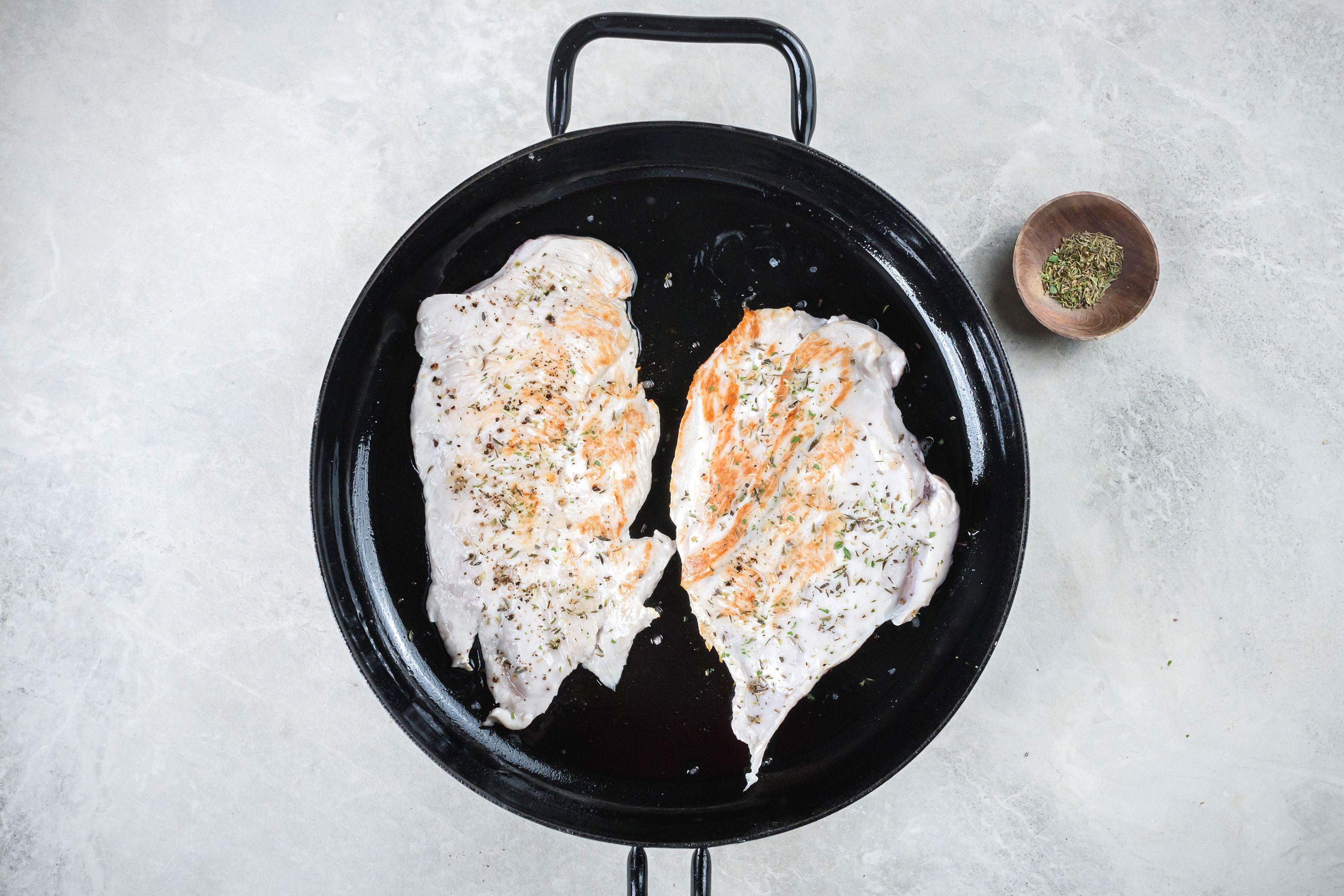 Turkey breasts in skillet with sprinkled herbs