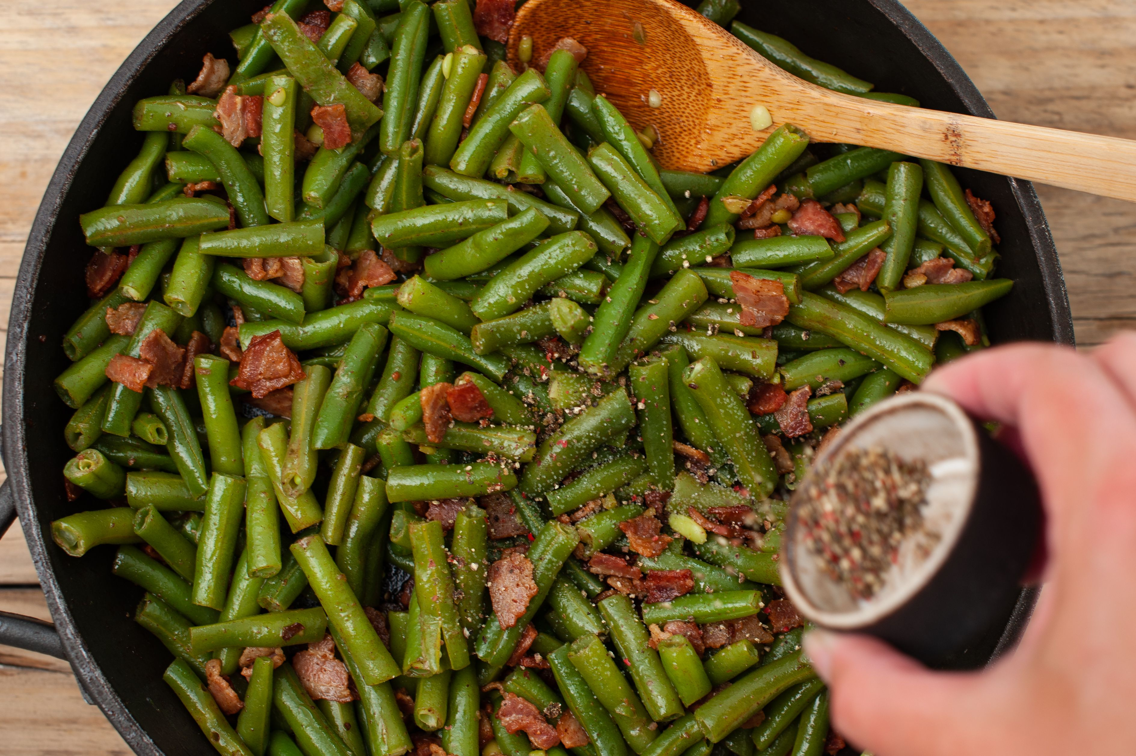 Adding seasoning to the bacon and green beans