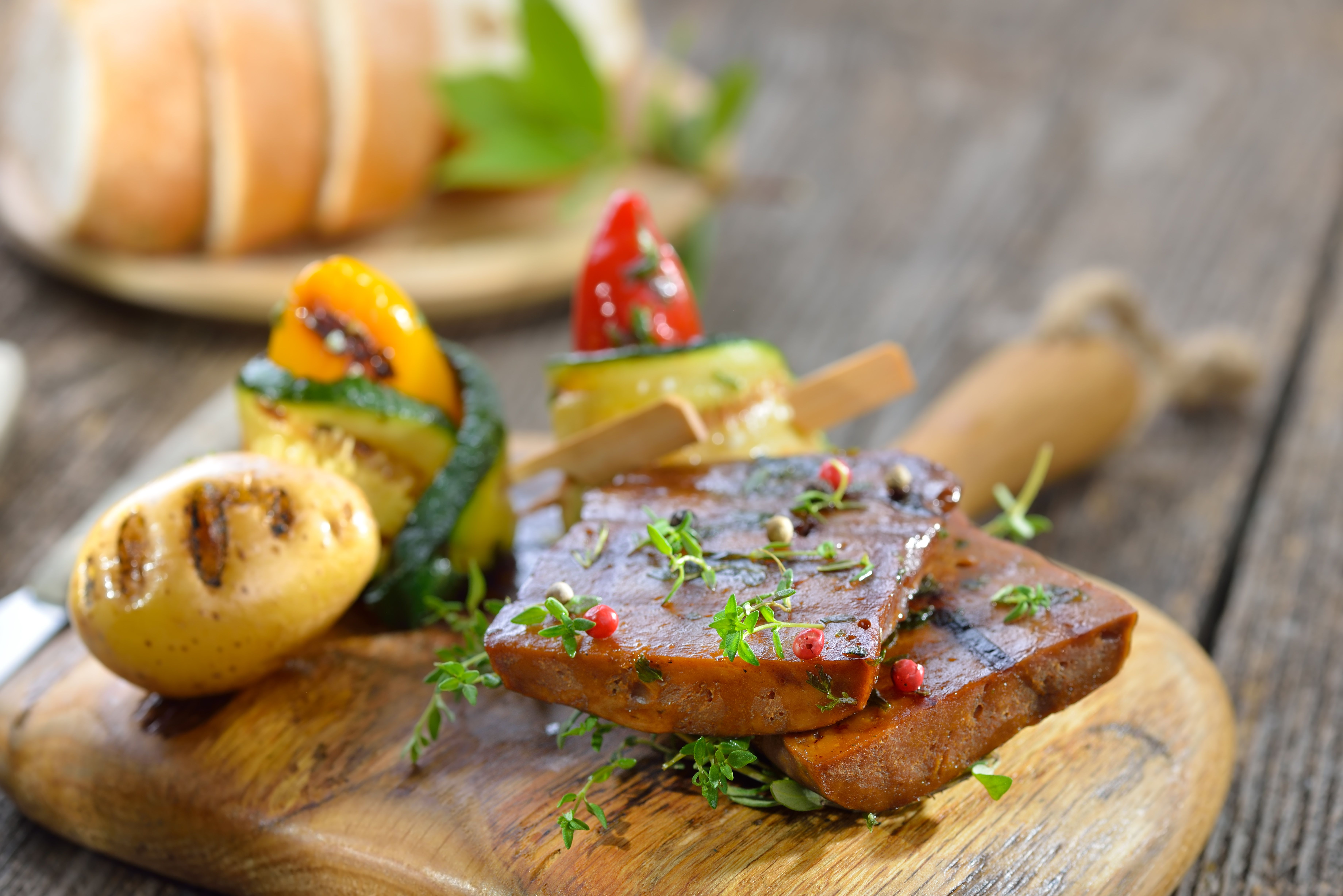 Grilled seitan steaks on a cutting board with vegetables