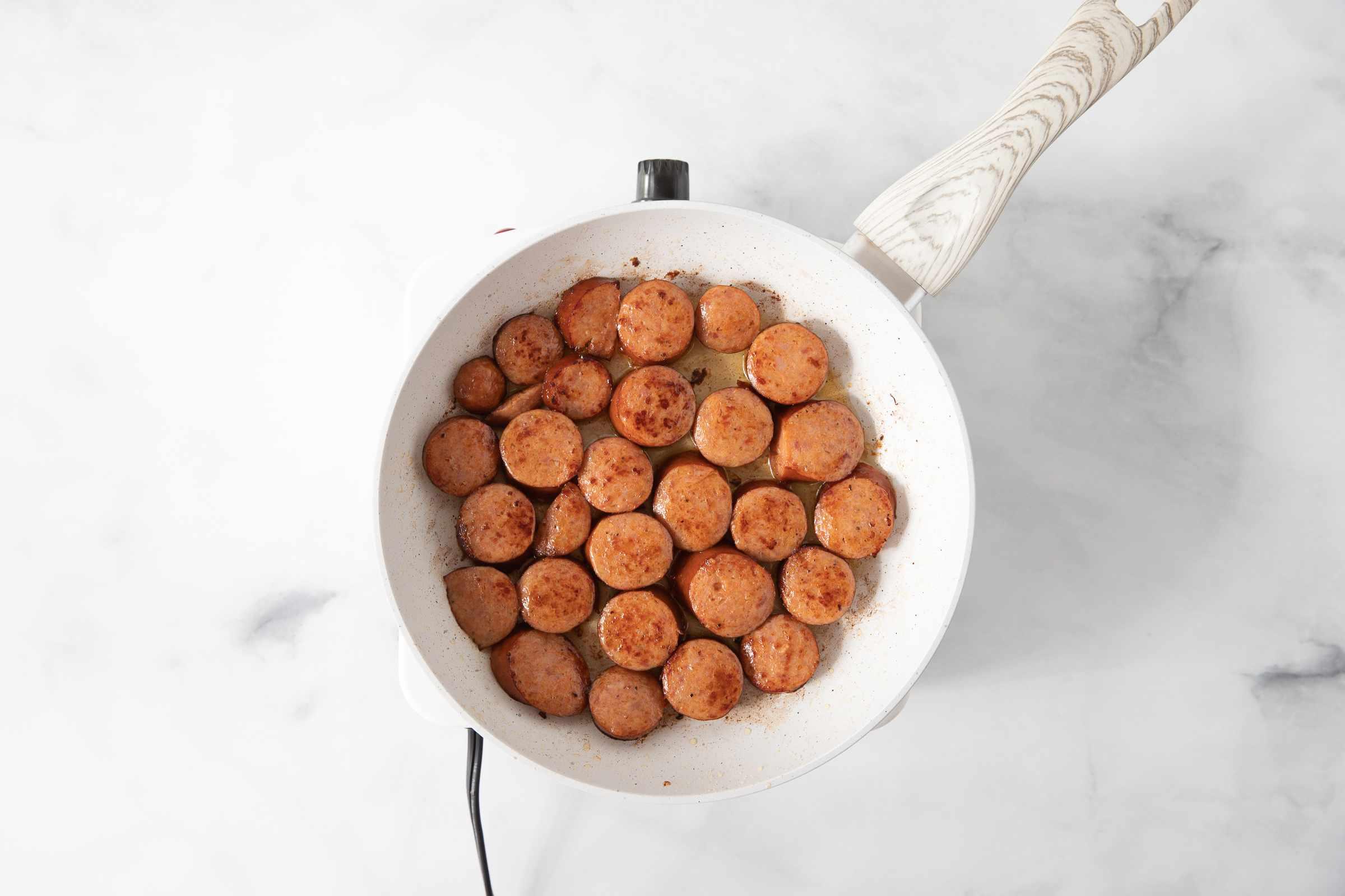 Brown sliced sausage in skillet
