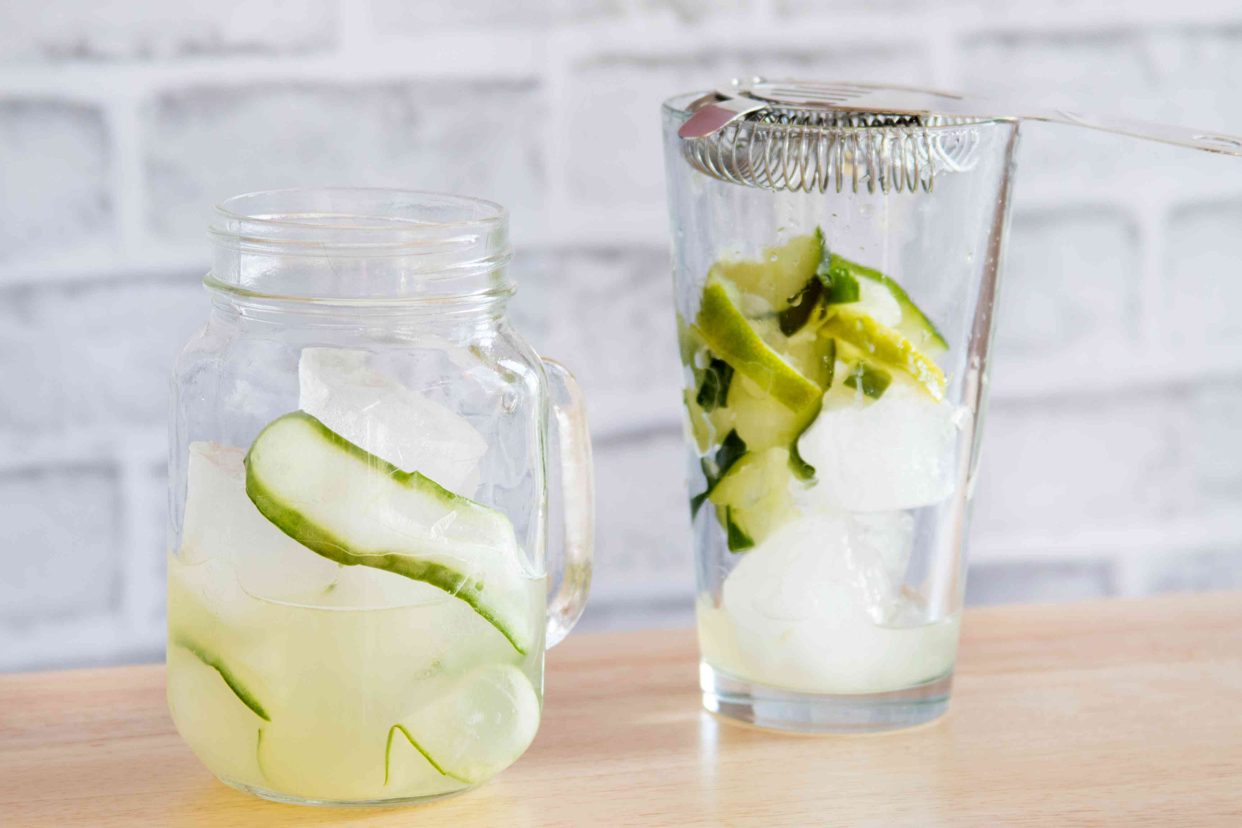 Straining a Cucumber Collins Cocktail