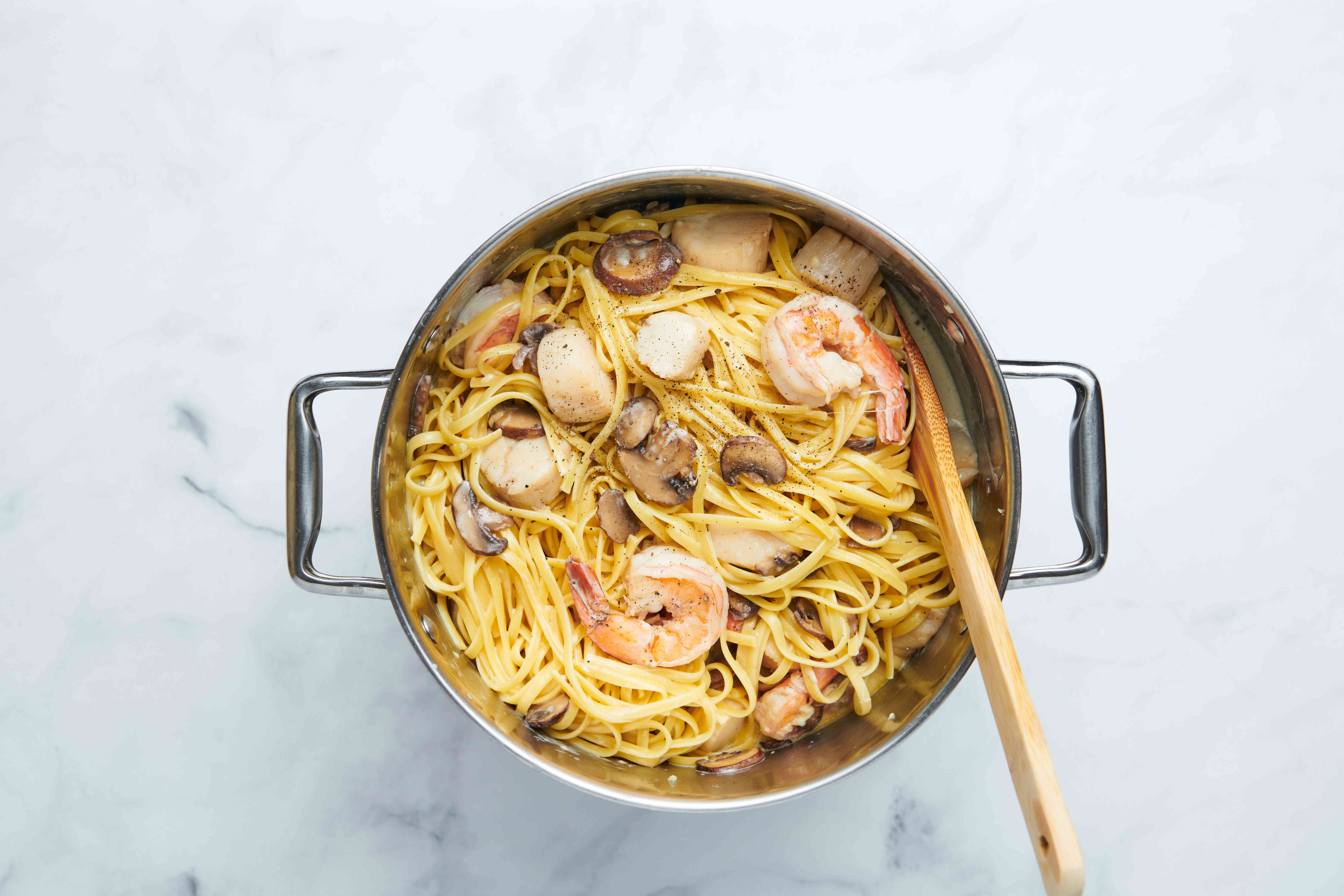 pasta with mushrooms and seafood in a pot