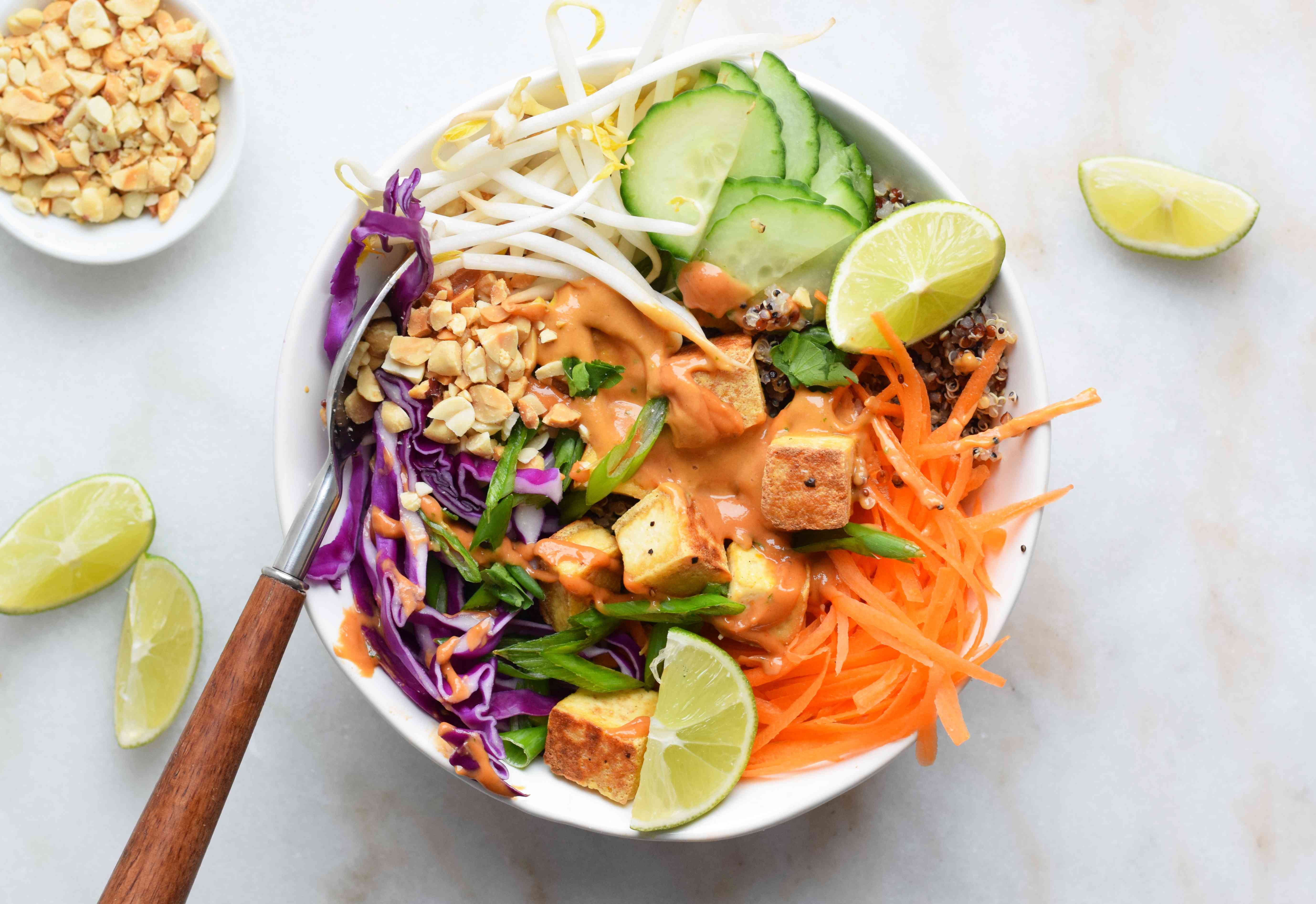 buddha bowl topped with veggies and lime wedges