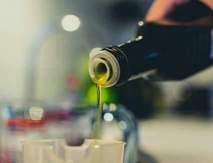 Woman pouring olive oil in a jar