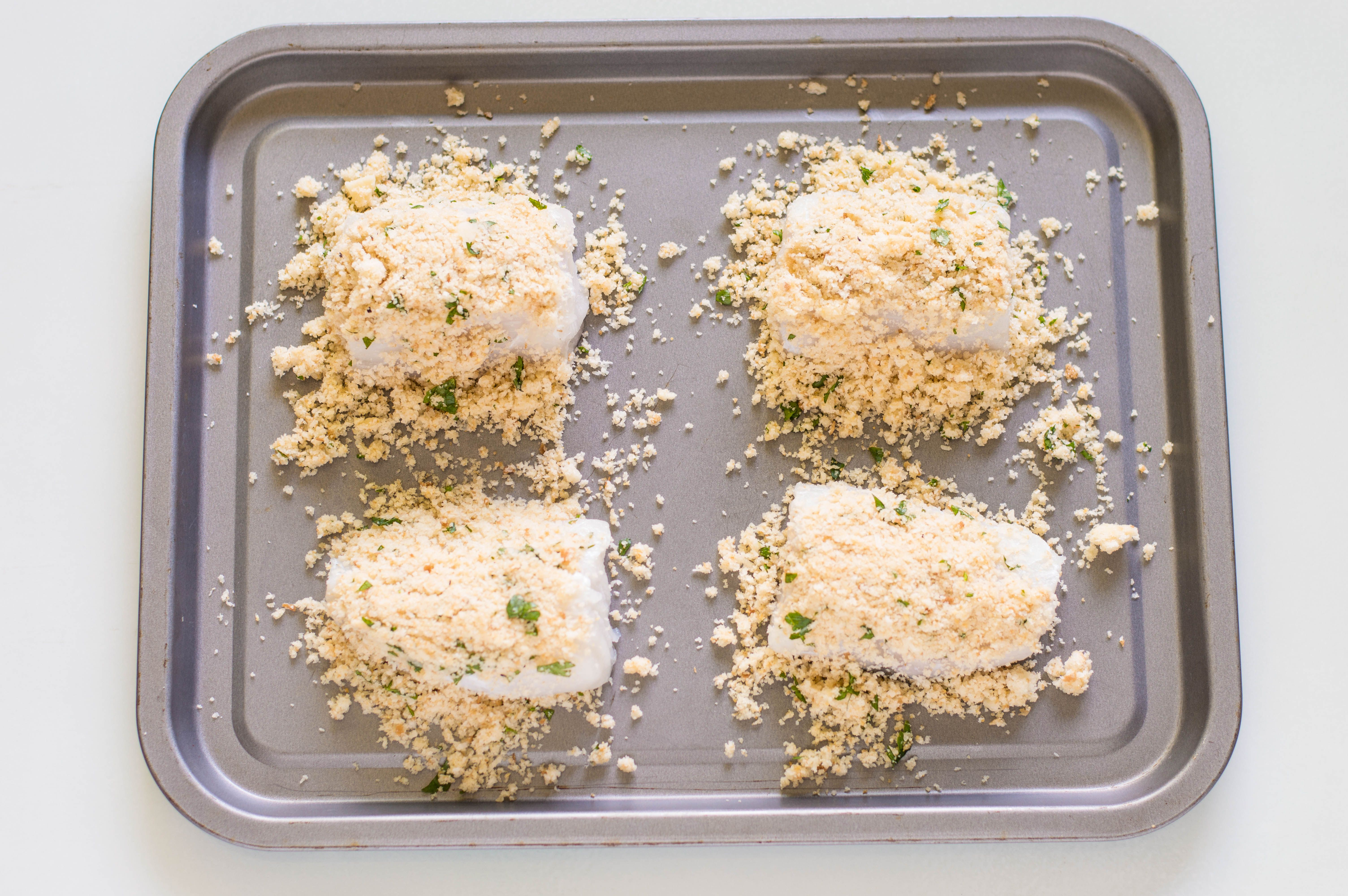 Breadcrumbs sprinkled on halibut fillets on a rimmed baking sheet