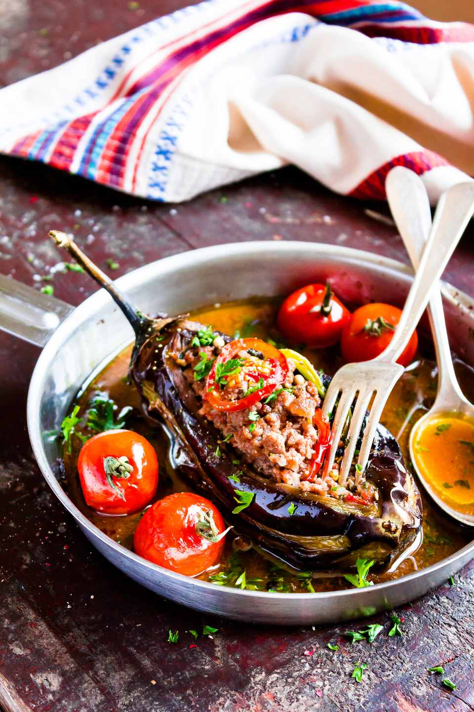 Baked aubergine or eggplant stuffed with minced pork and beef, carrot, pepper, cherry tomatoes in a pan on a wooden table