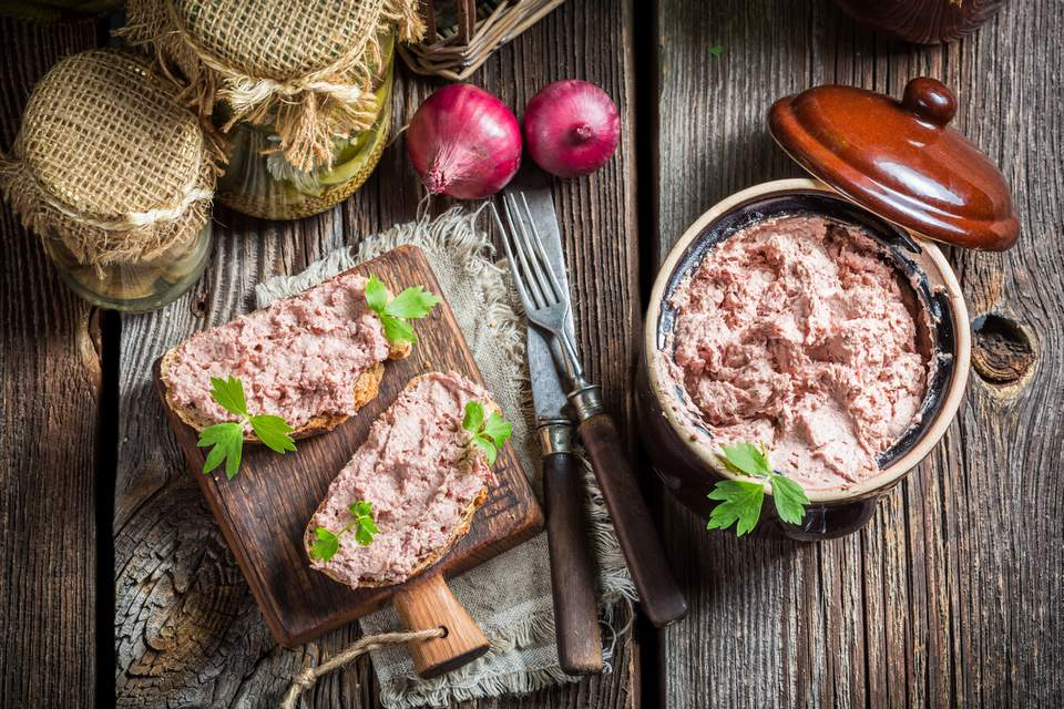 Pot of pâté next to bread topped with pâté