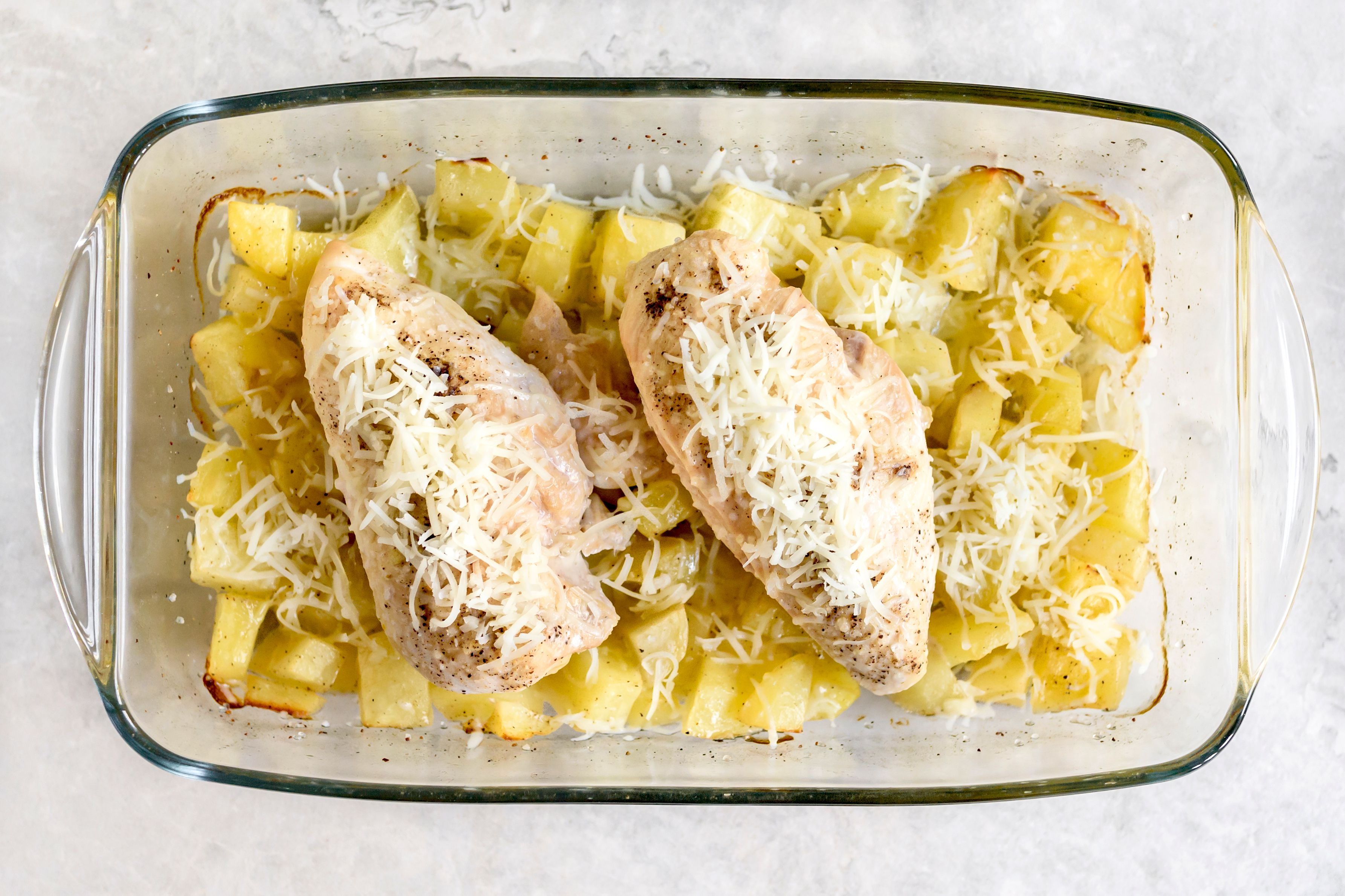 Chicken and potatoes topped with shredded Parmesan
