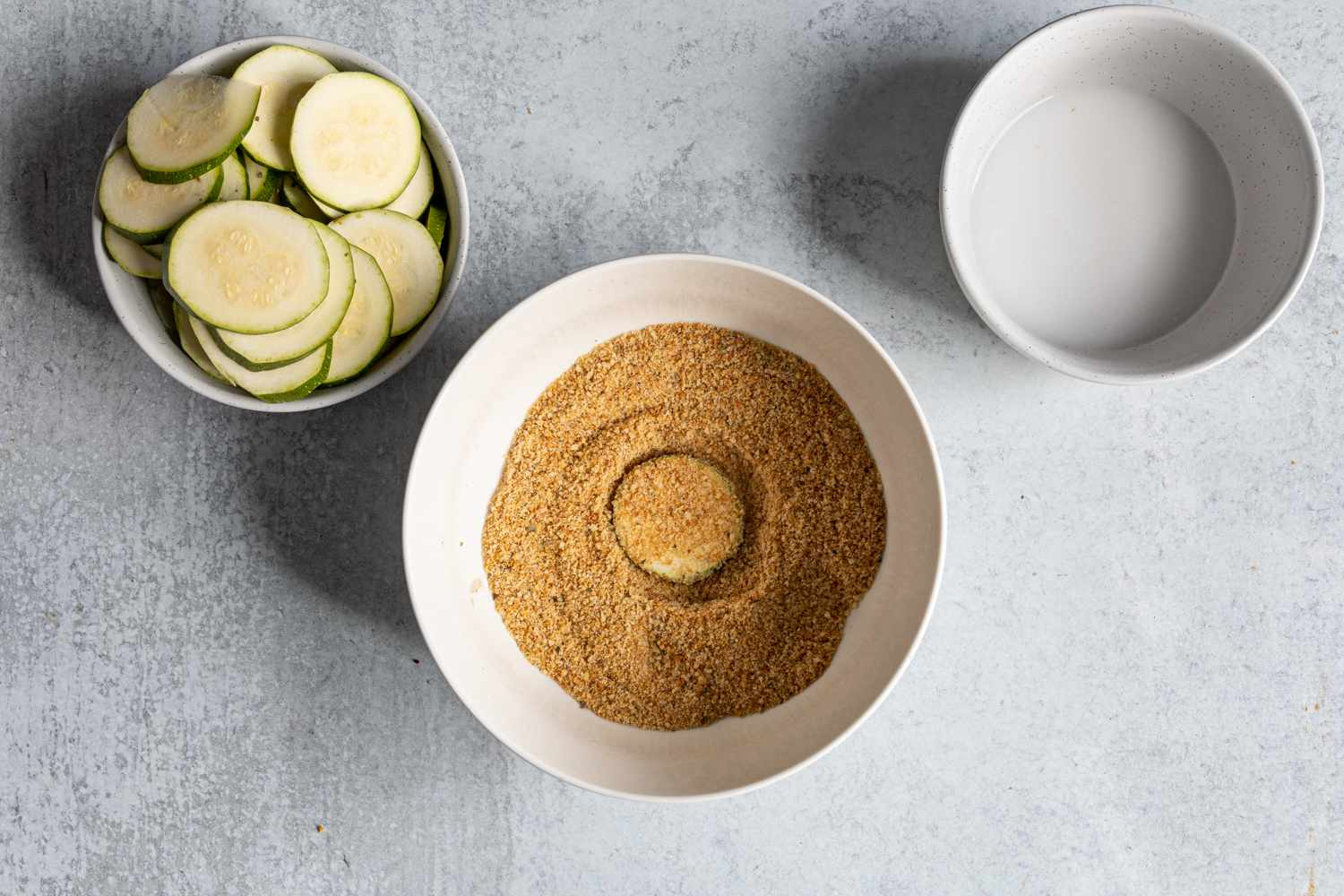zucchini piece dipped into breadcrumbs