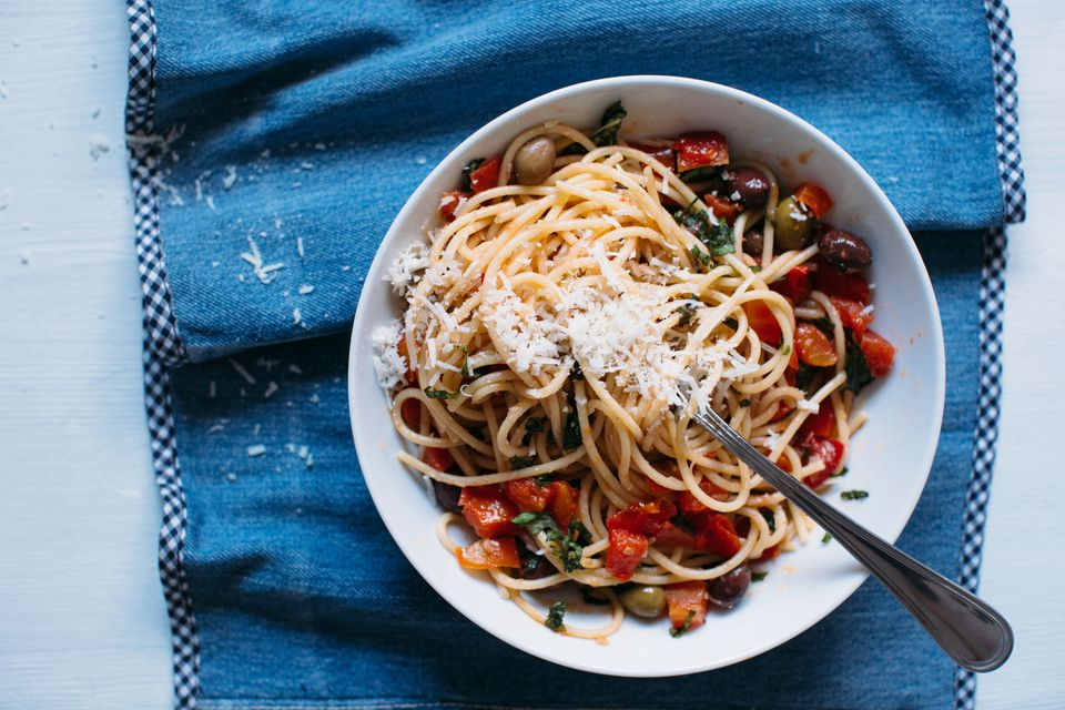 spaghetti pasta with fresh tomatoes, olives and parmesan