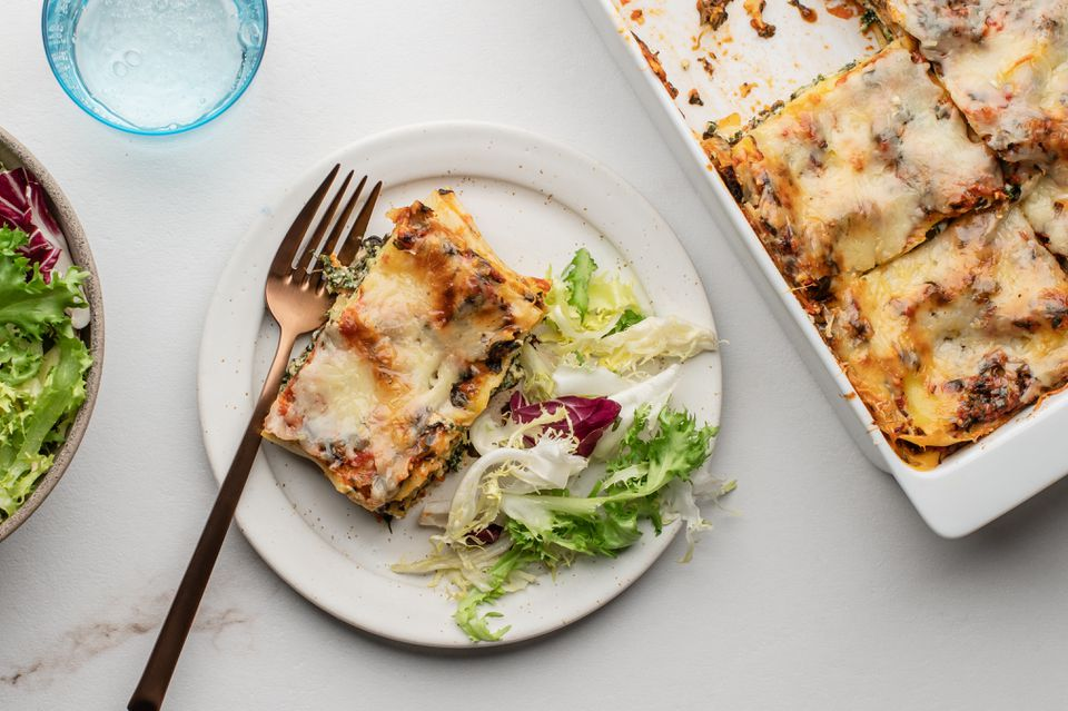 Perfect spinach lasagna on a plate with salad greens