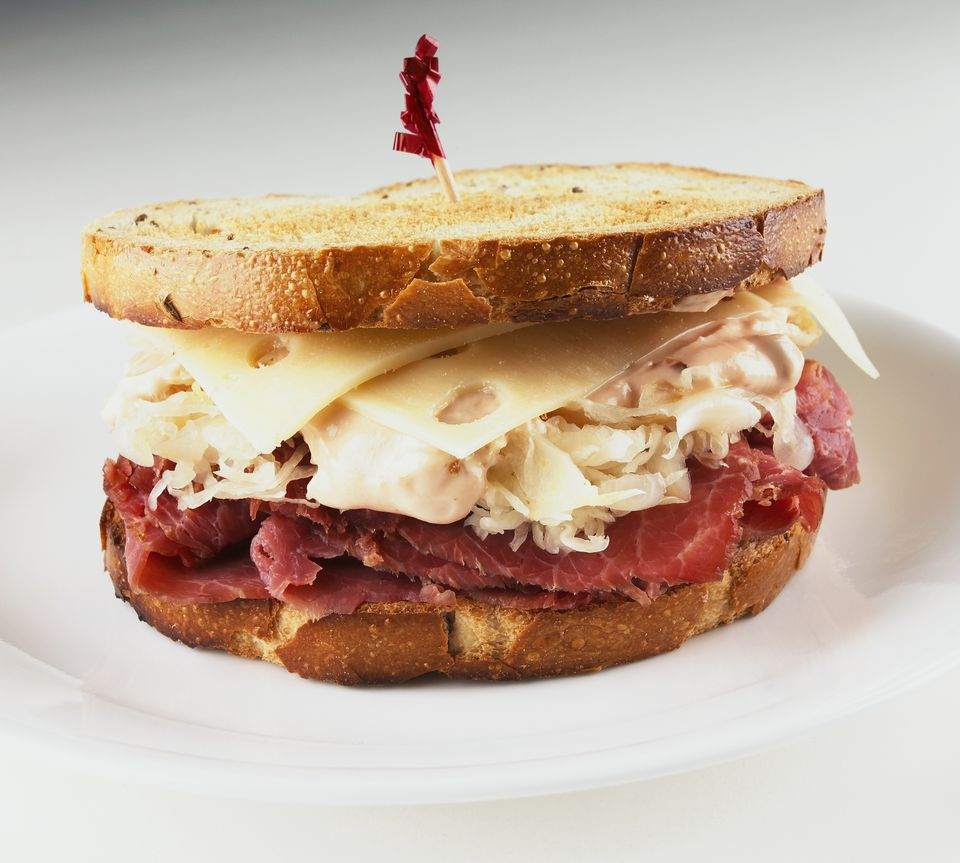 Reuben sandwich with a red toothpick on a white background