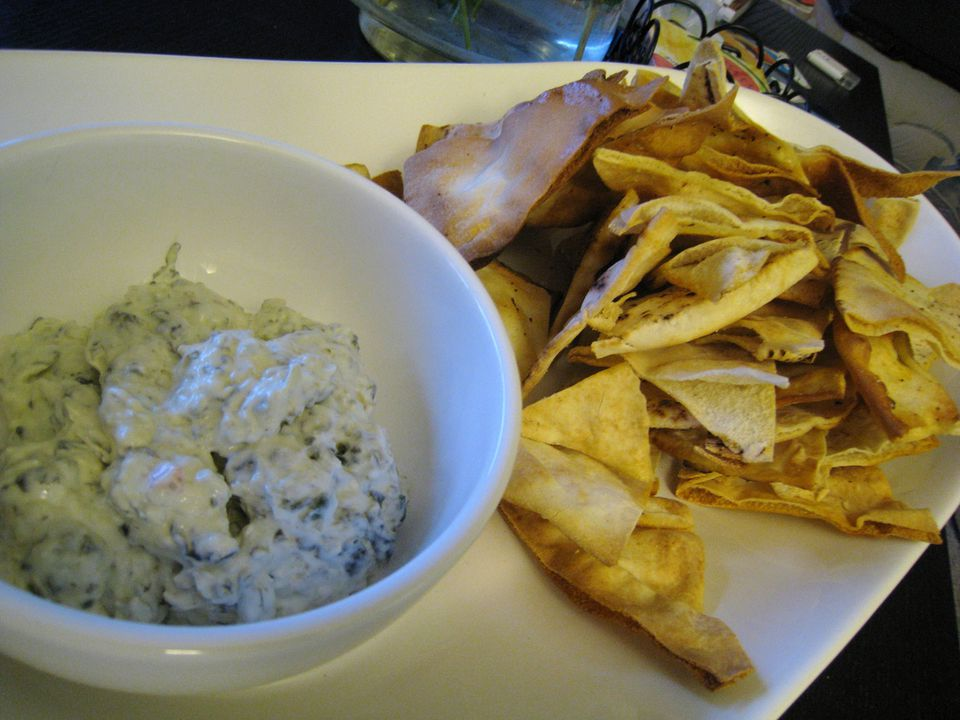 A bowl of spinach dip with pita chips