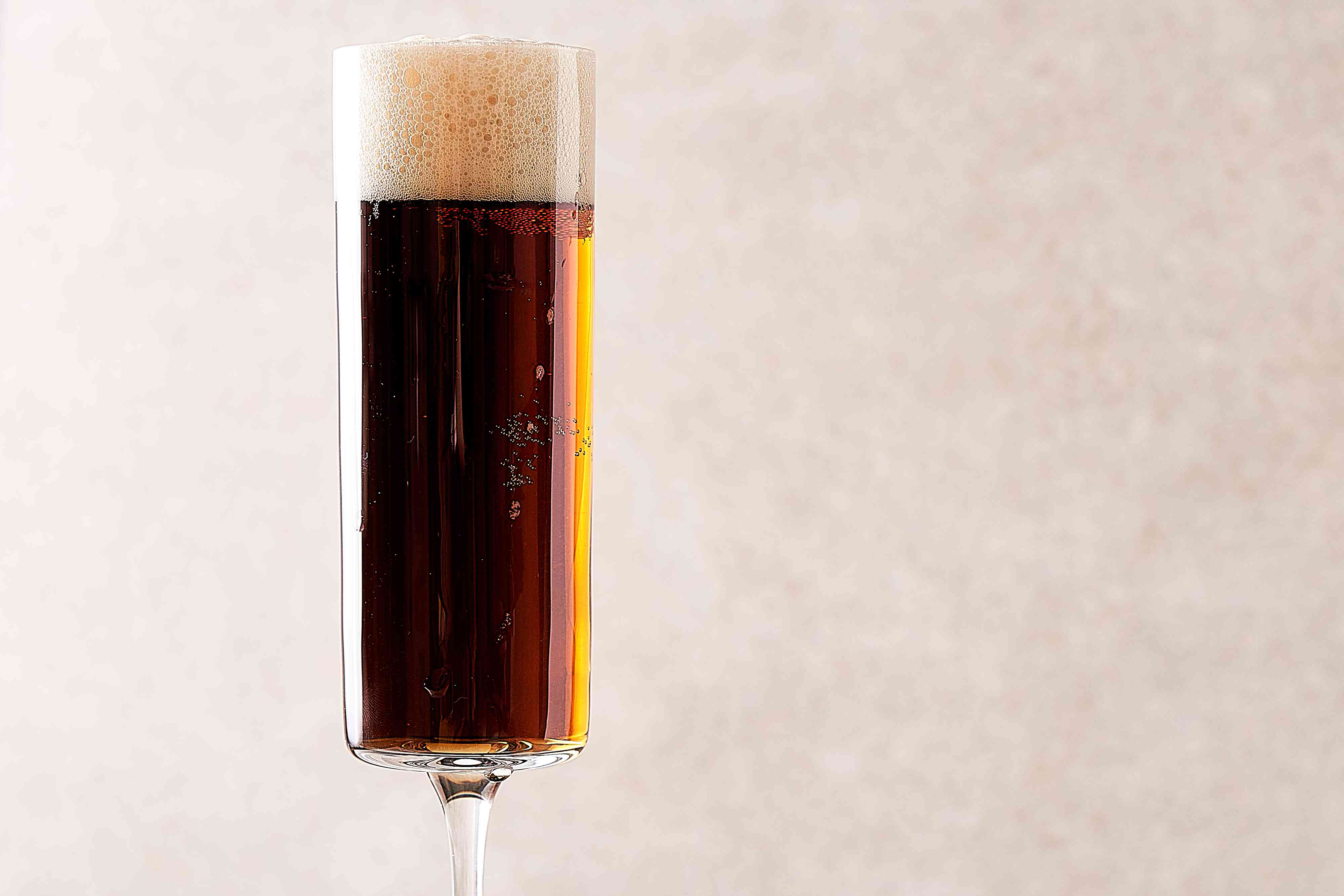 stout poured on top of champagne in glass