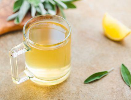 Sage tea in a glass mug with sage and lemon
