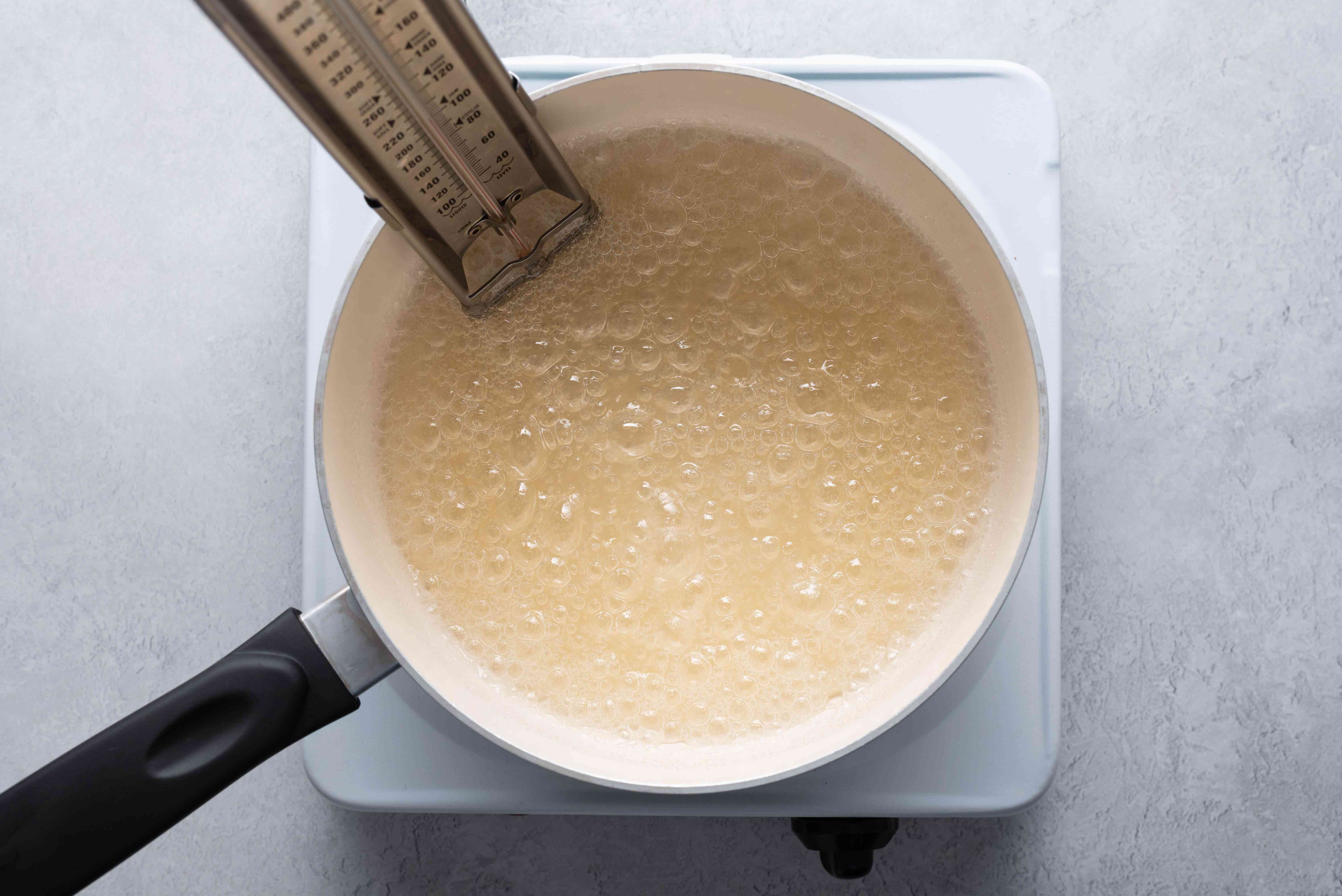 sugar syrup on stove with candy thermometer
