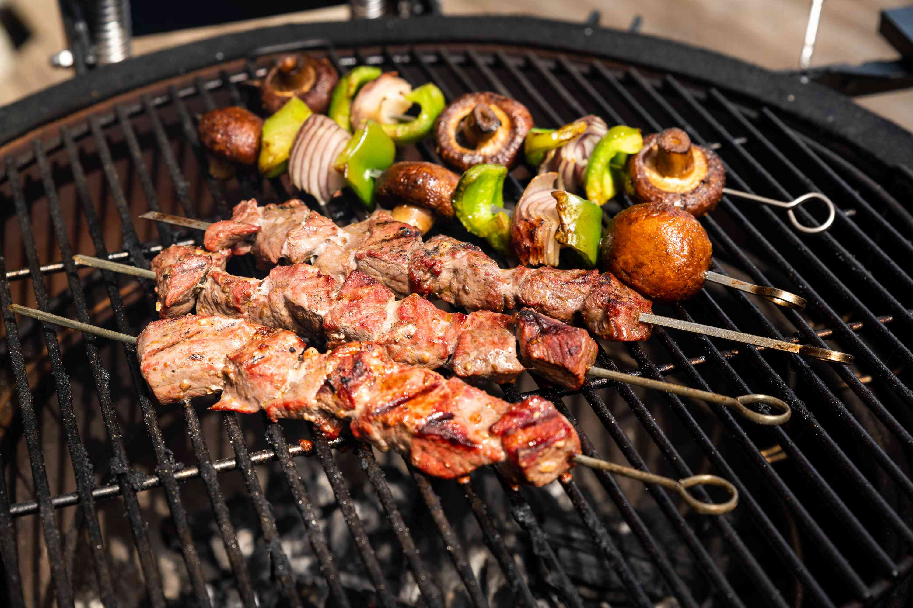 beef and vegetable skewers cooking on a grill