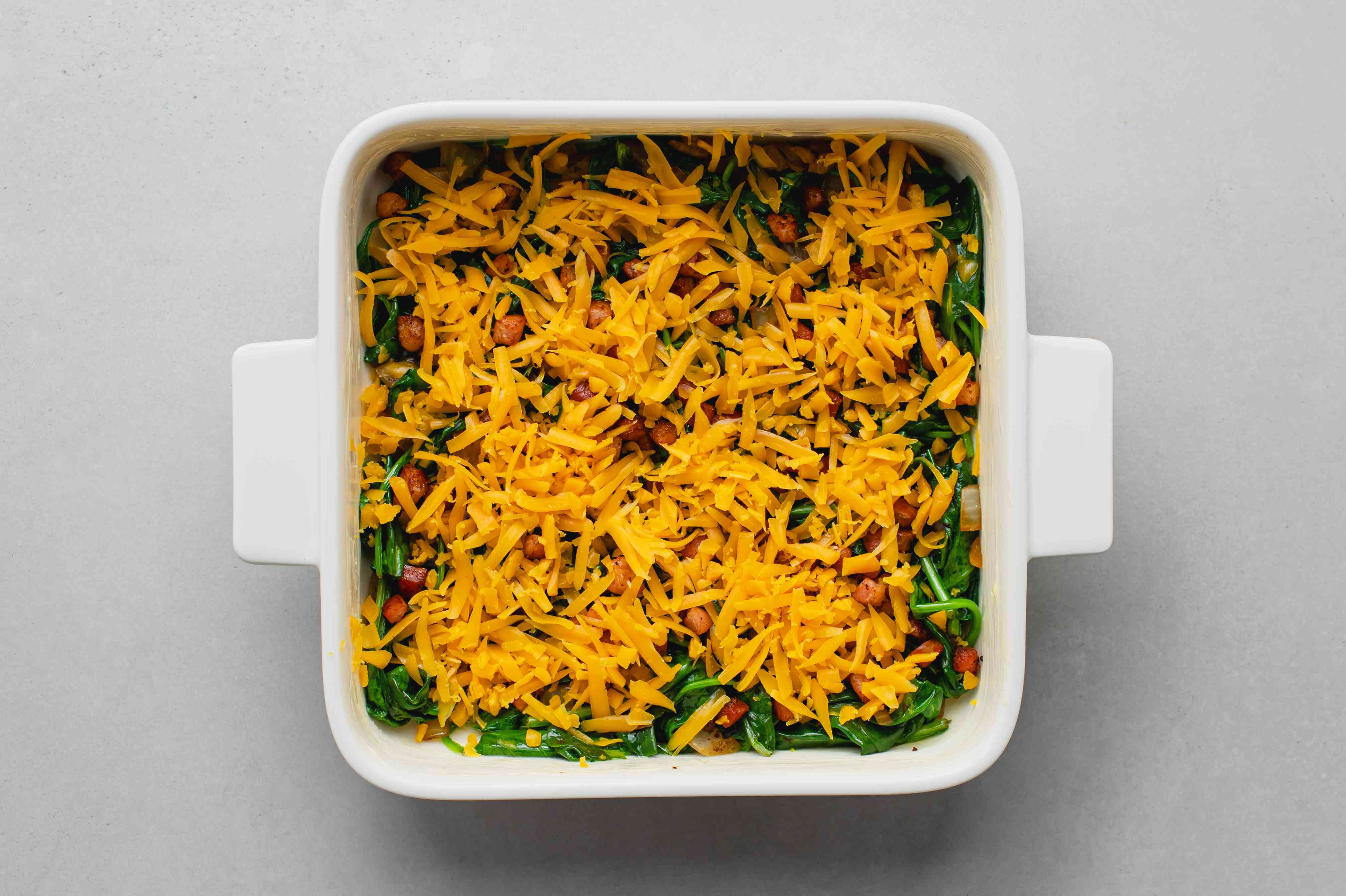 spinach, bacon and cheese in a baking dish