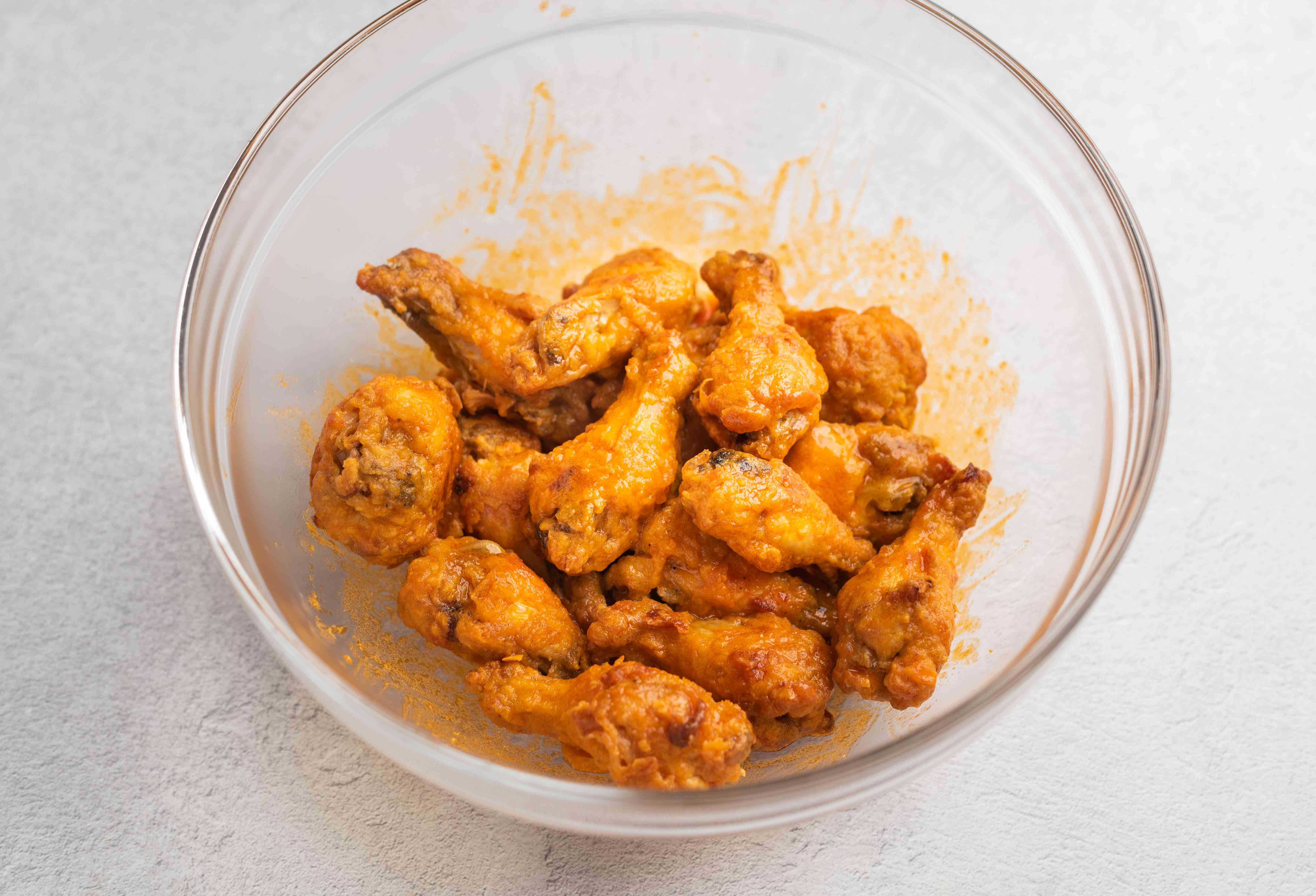Wings tossed with sauce in a bowl