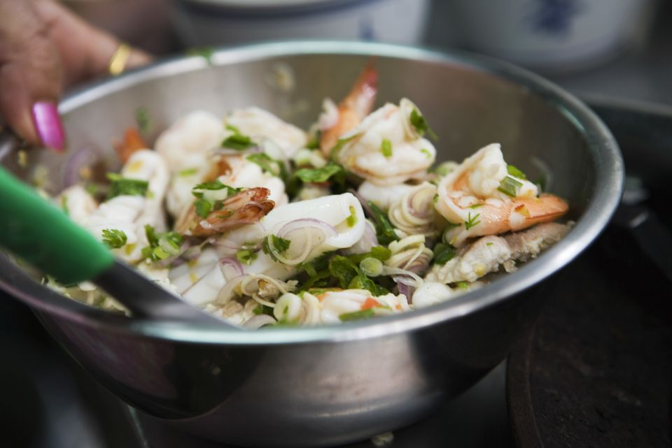 Preparing seafood salad with mint