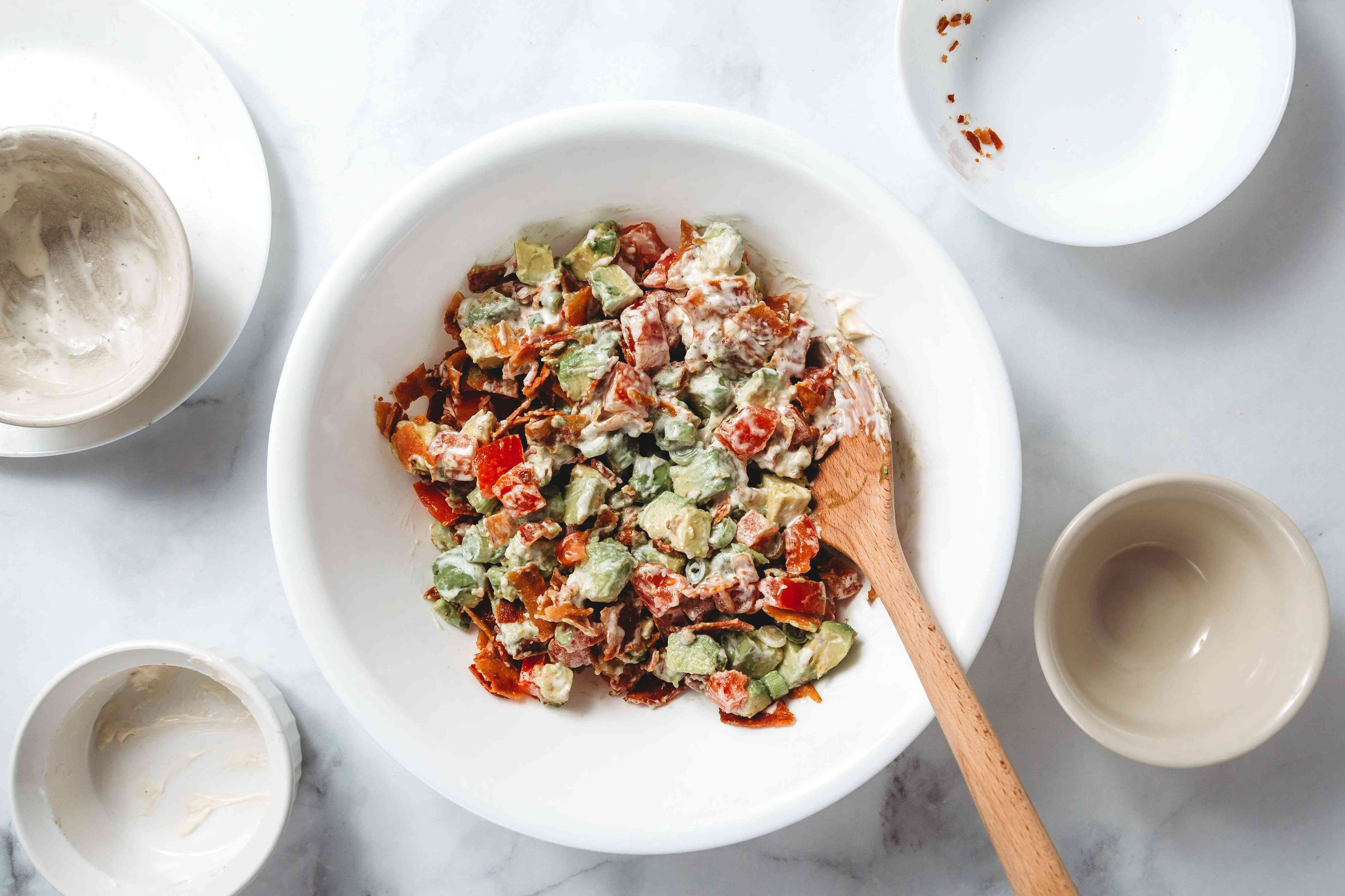 Tomatoes, avocado, green onion, cooked bacon, ranch dressing, and mayonnaise in a bowl