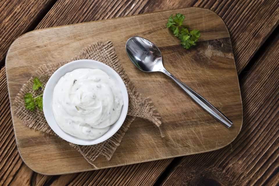 sour cream dip in bowl on wooden board