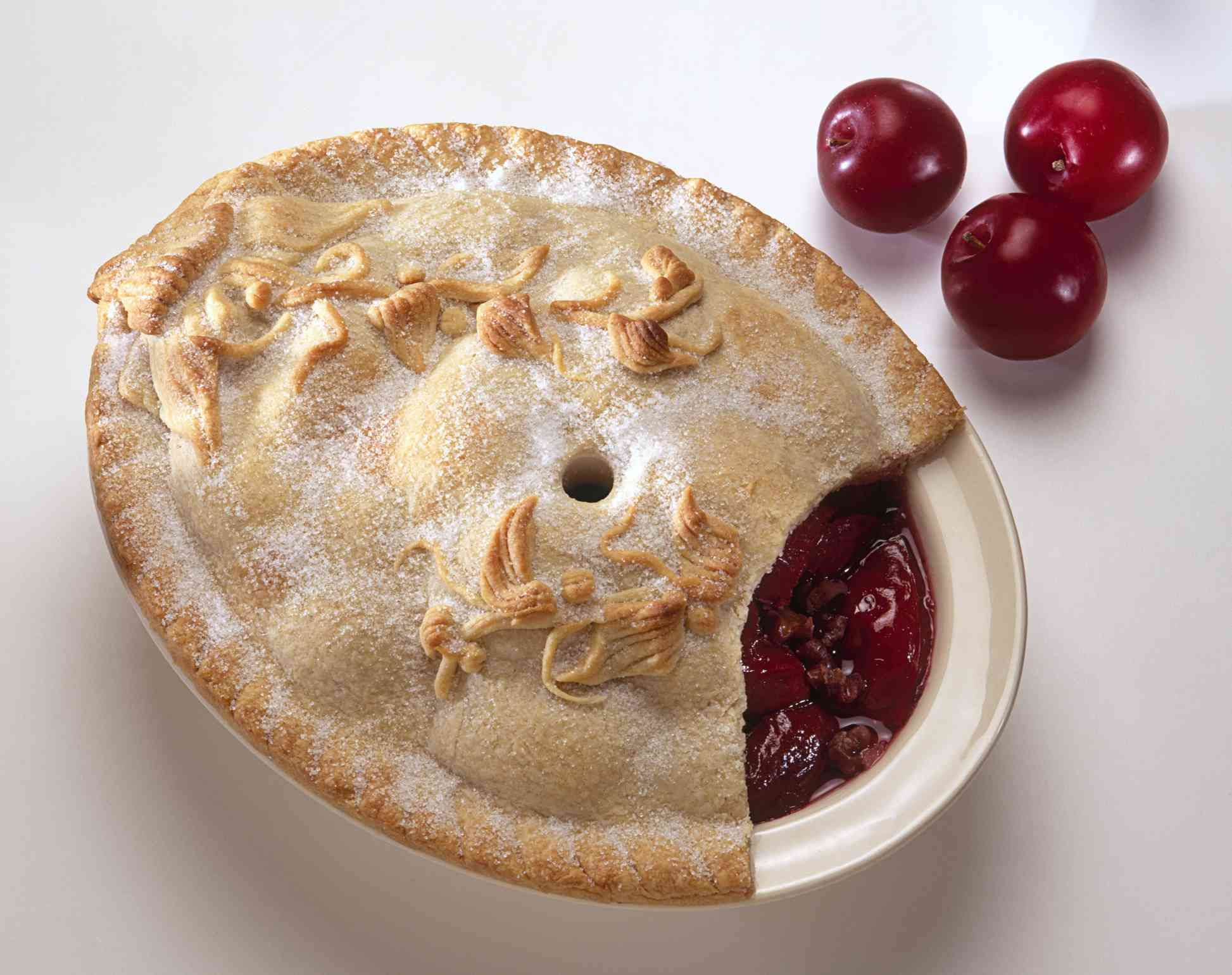 Plum pie with leafy decorated crust and fresh fruit