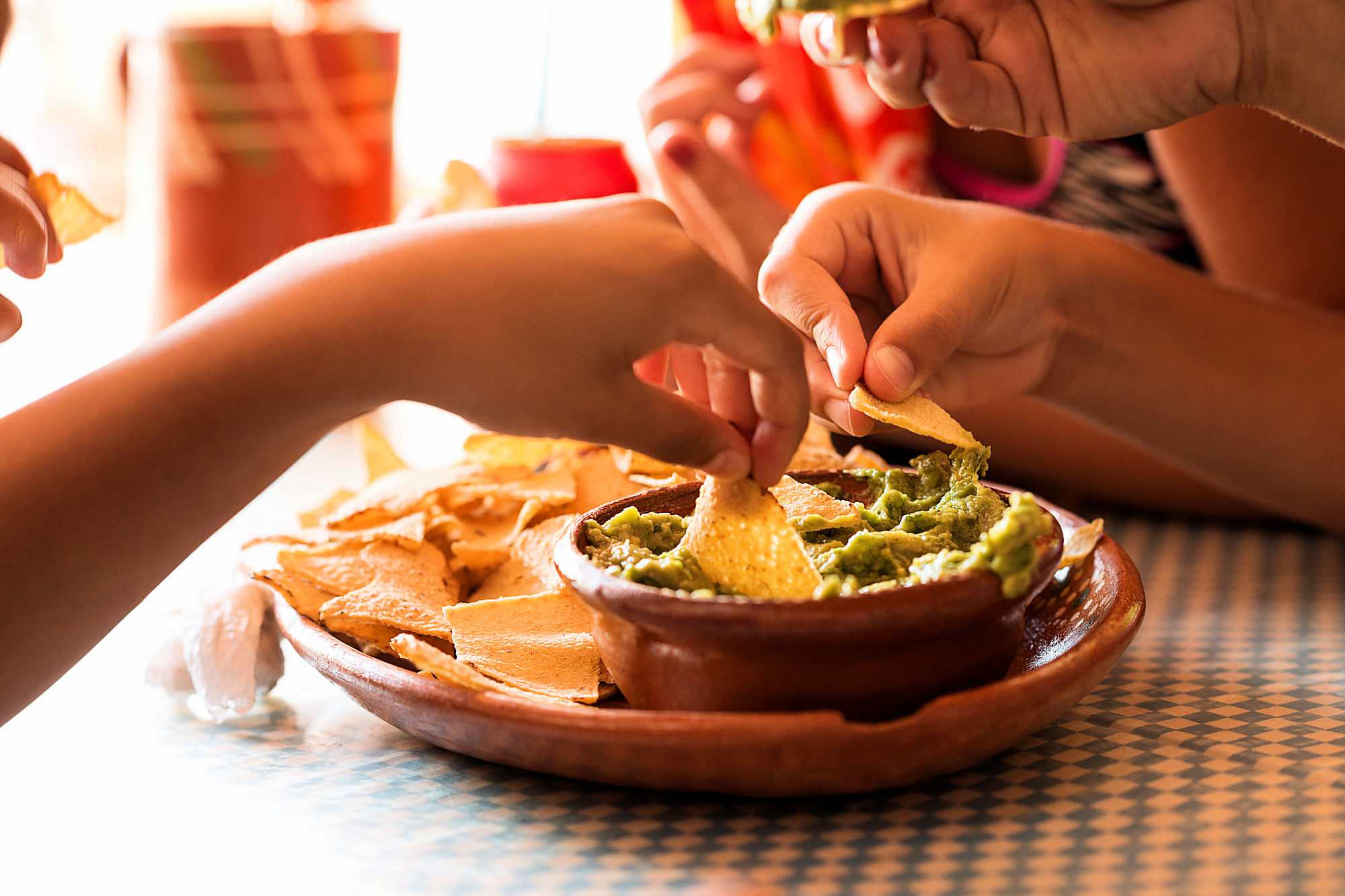 People eating chips and guacamole.