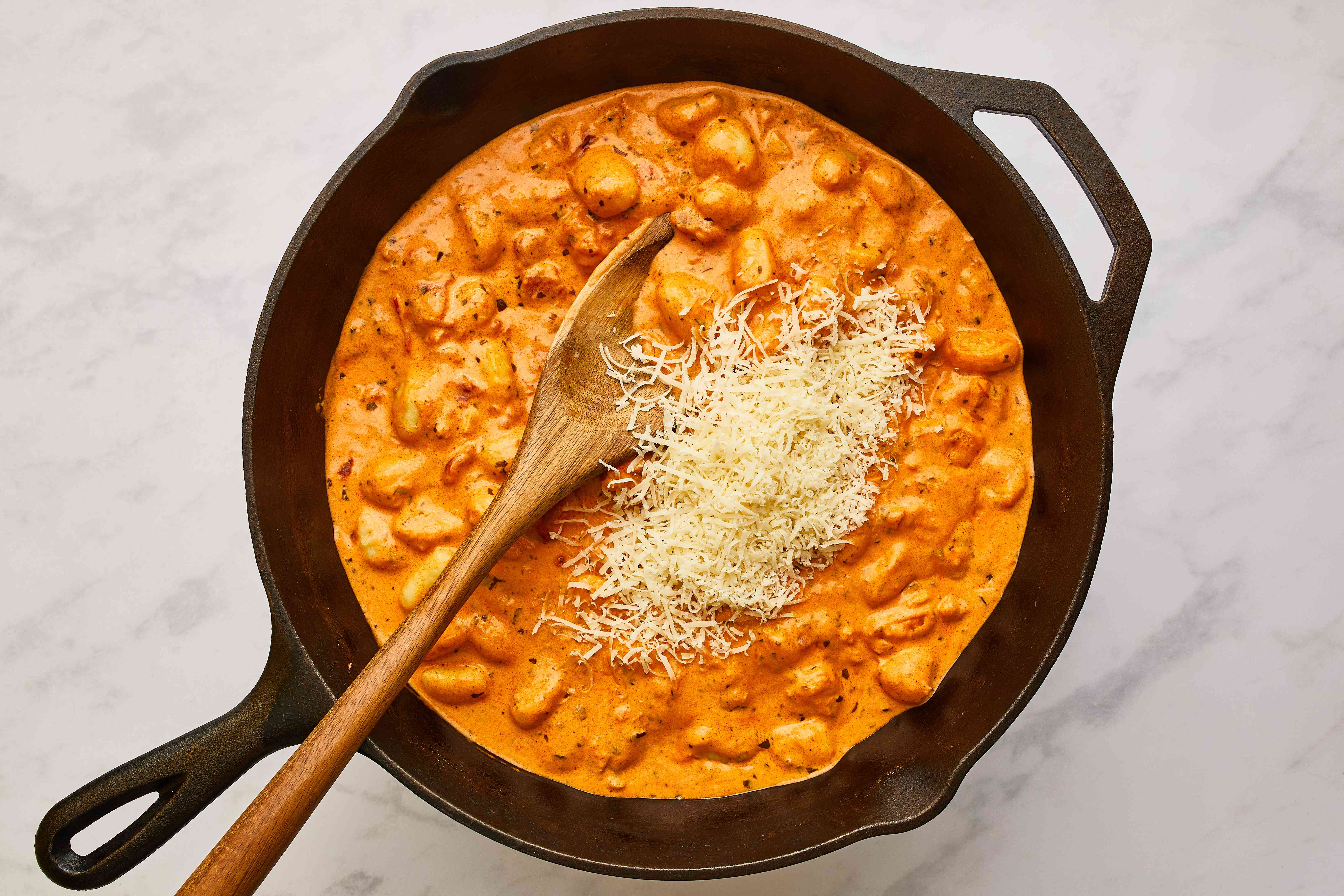Add the freshly grated Parmigiano-Reggiano to the sauce and gnocchi
