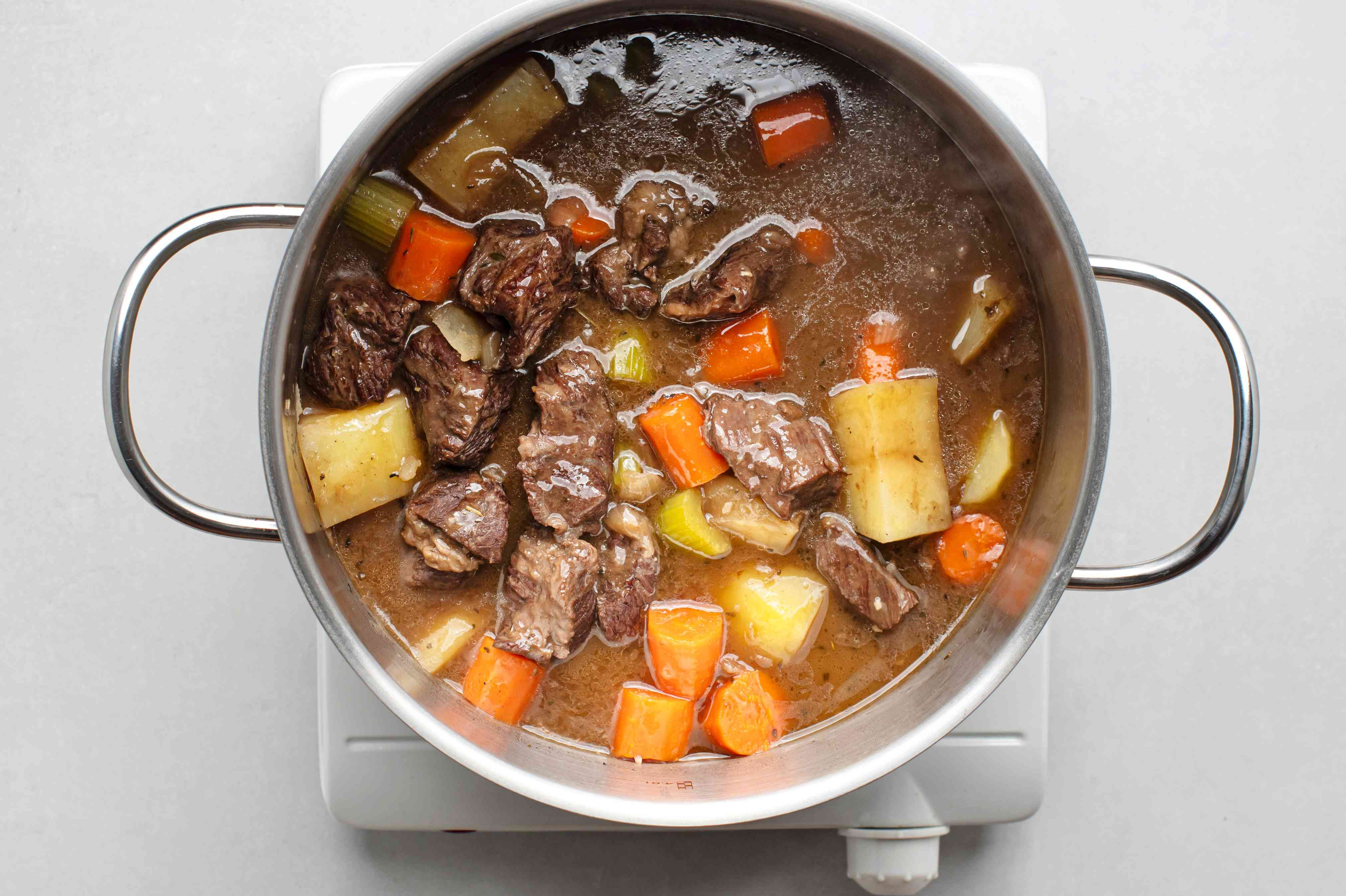 Add vegetables to the beef mixture in the pot