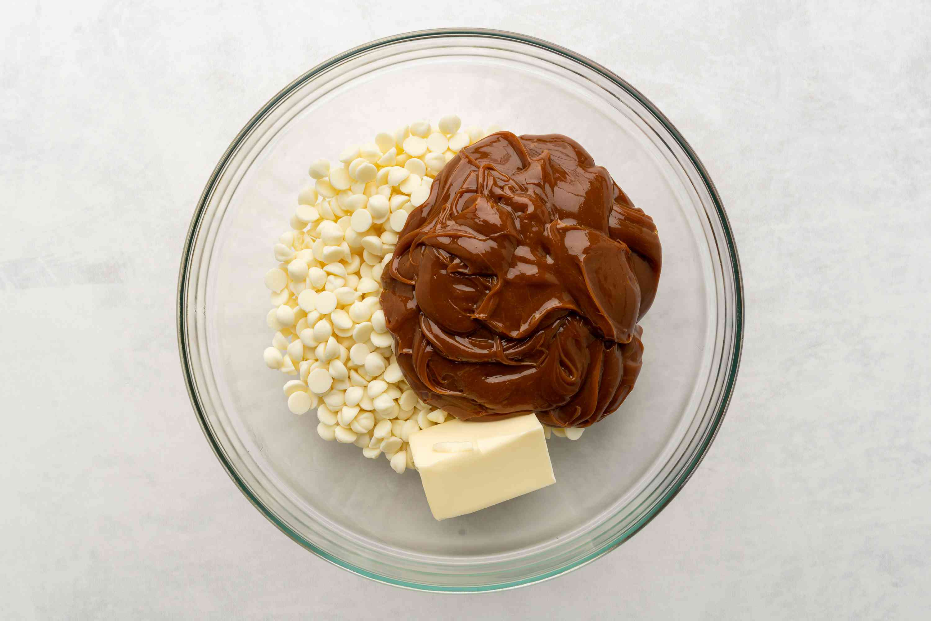 white chocolate chips, dulce de leche, and butter in a bowl