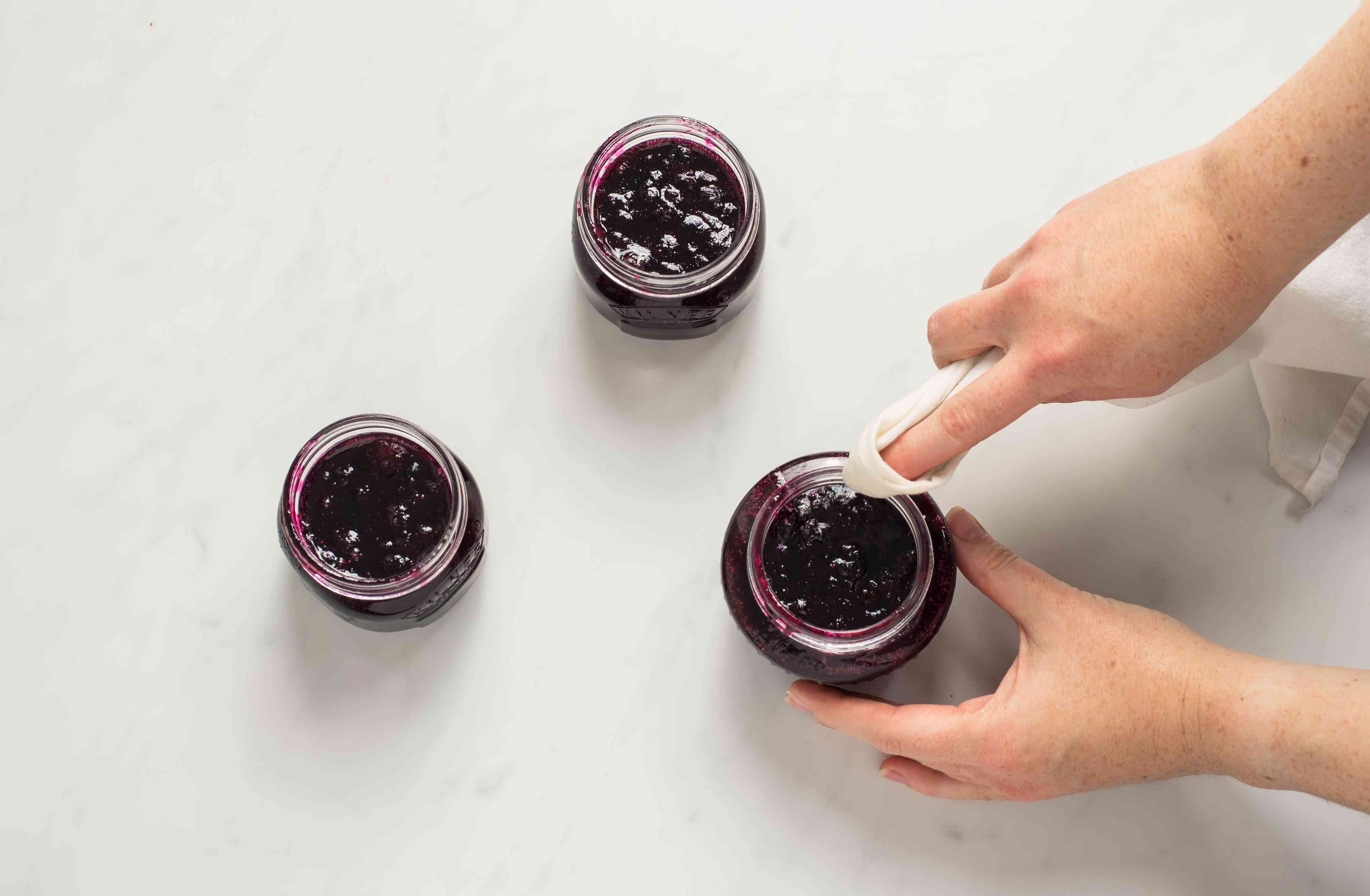 Wiping the rims of the jars with a damp cloth