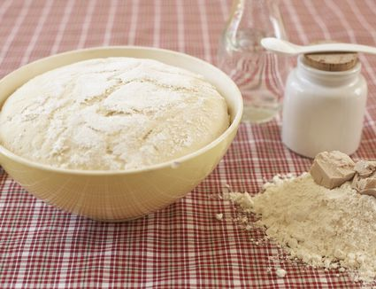 Bowl of raw yeast dough and ingredients of yeast dough on cloth
