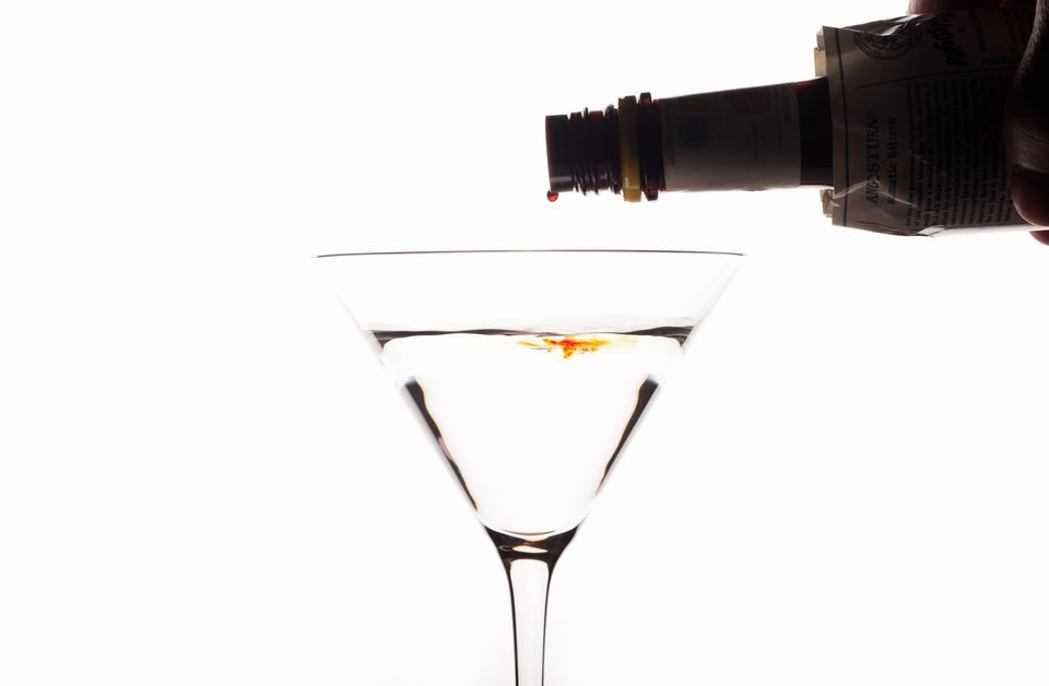 Angostura Bitters being poured into cocktail against white background