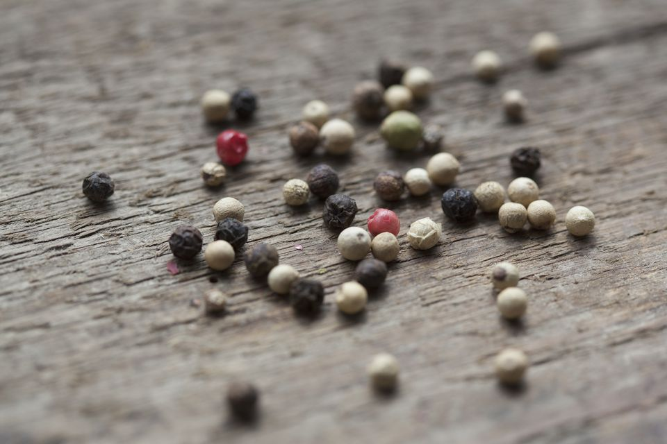 Variety of peppercorns on wooden table