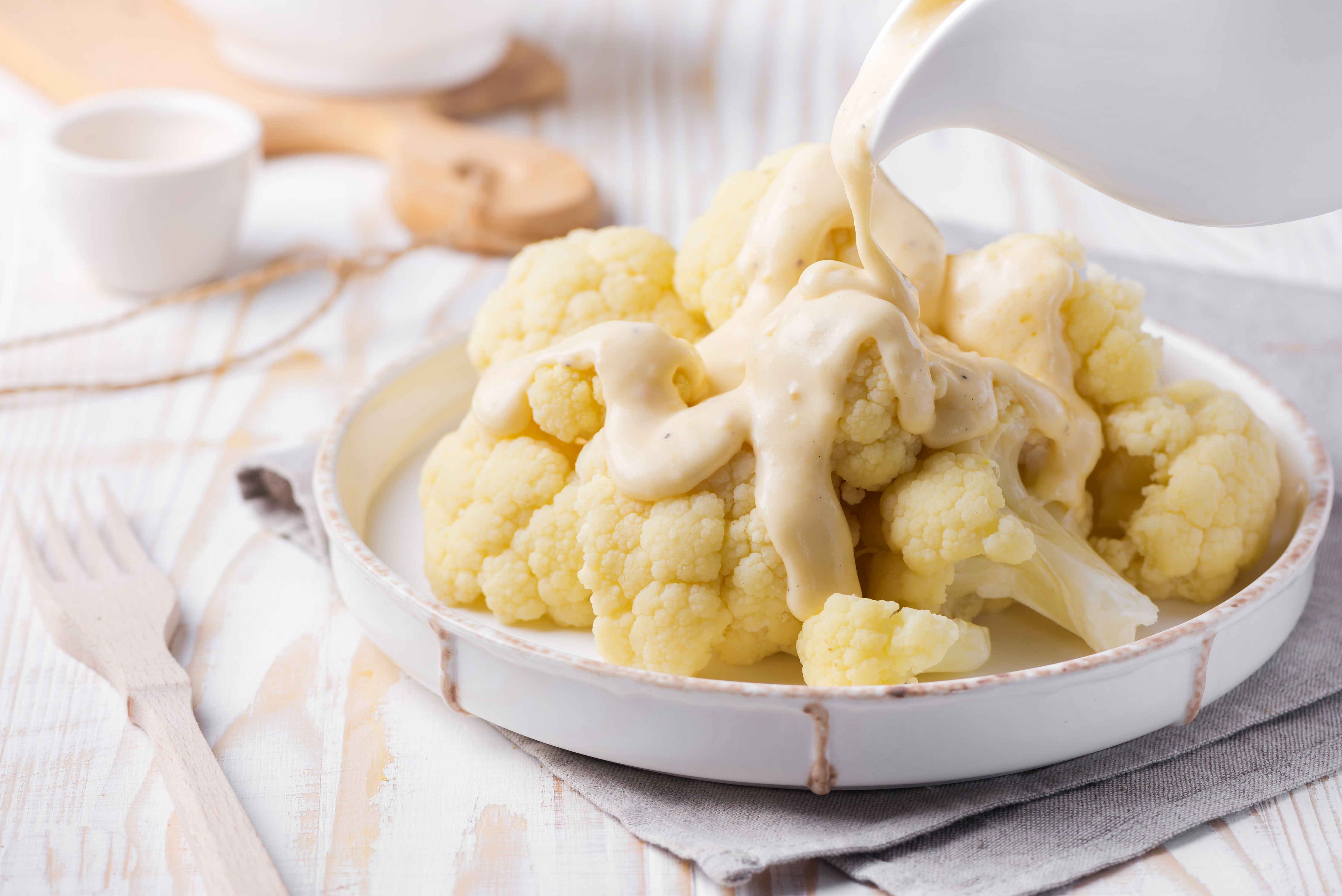 Cauliflower florets and cheese sauce in a serving dish