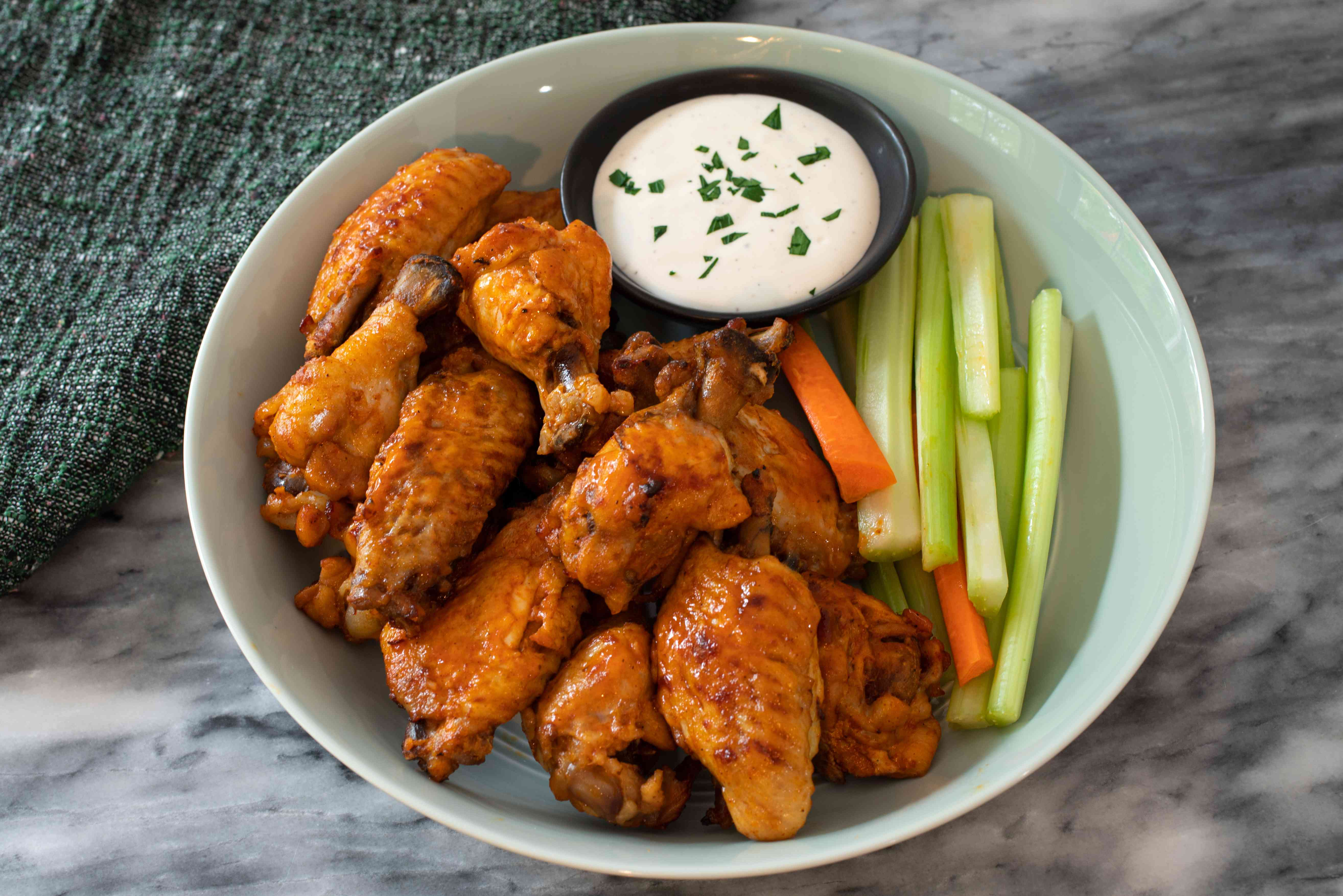 Buffalo wings made in an Instant Pot served with celery and carrot sticks and dip
