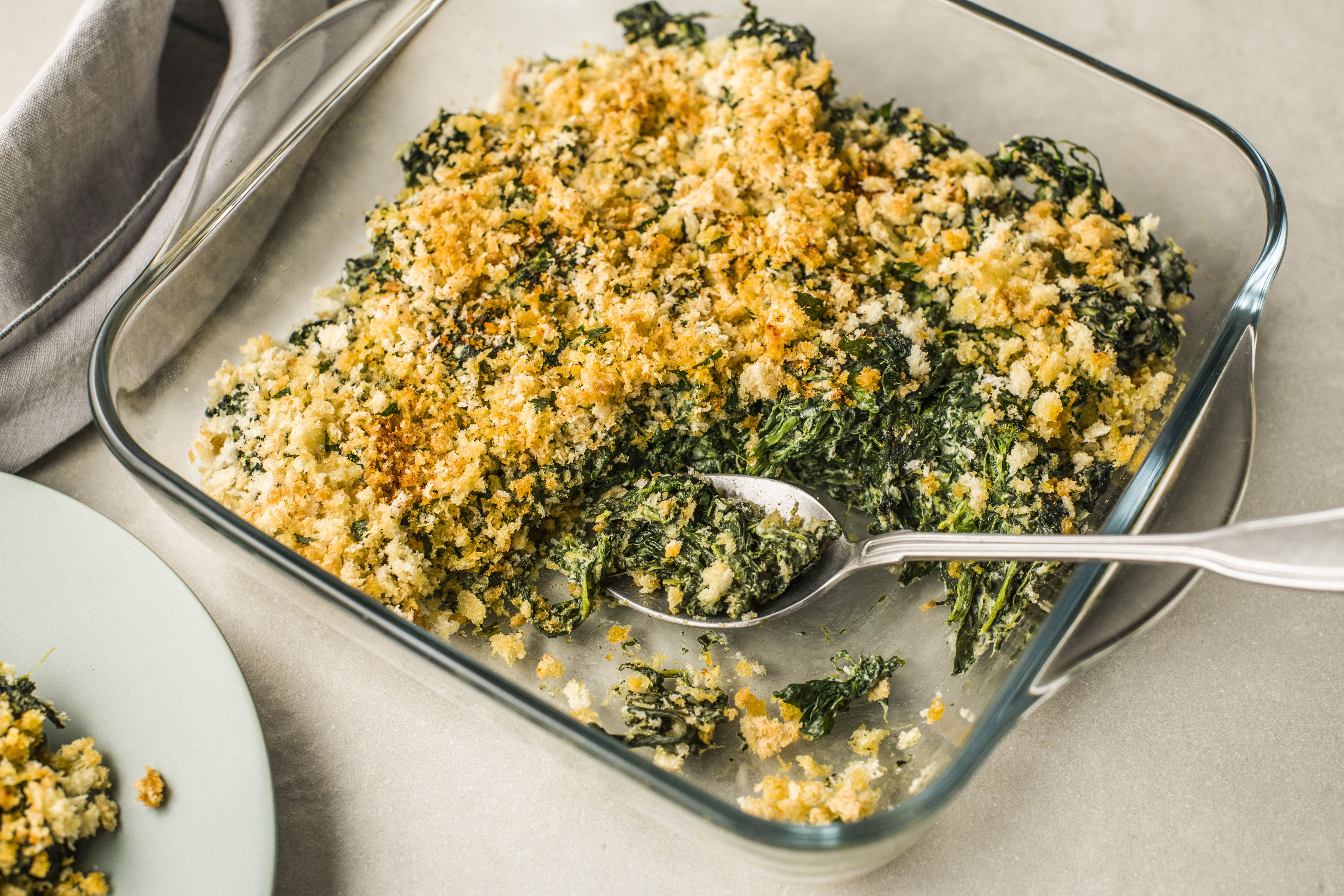 Serving spinach casserole from a glass baking dish