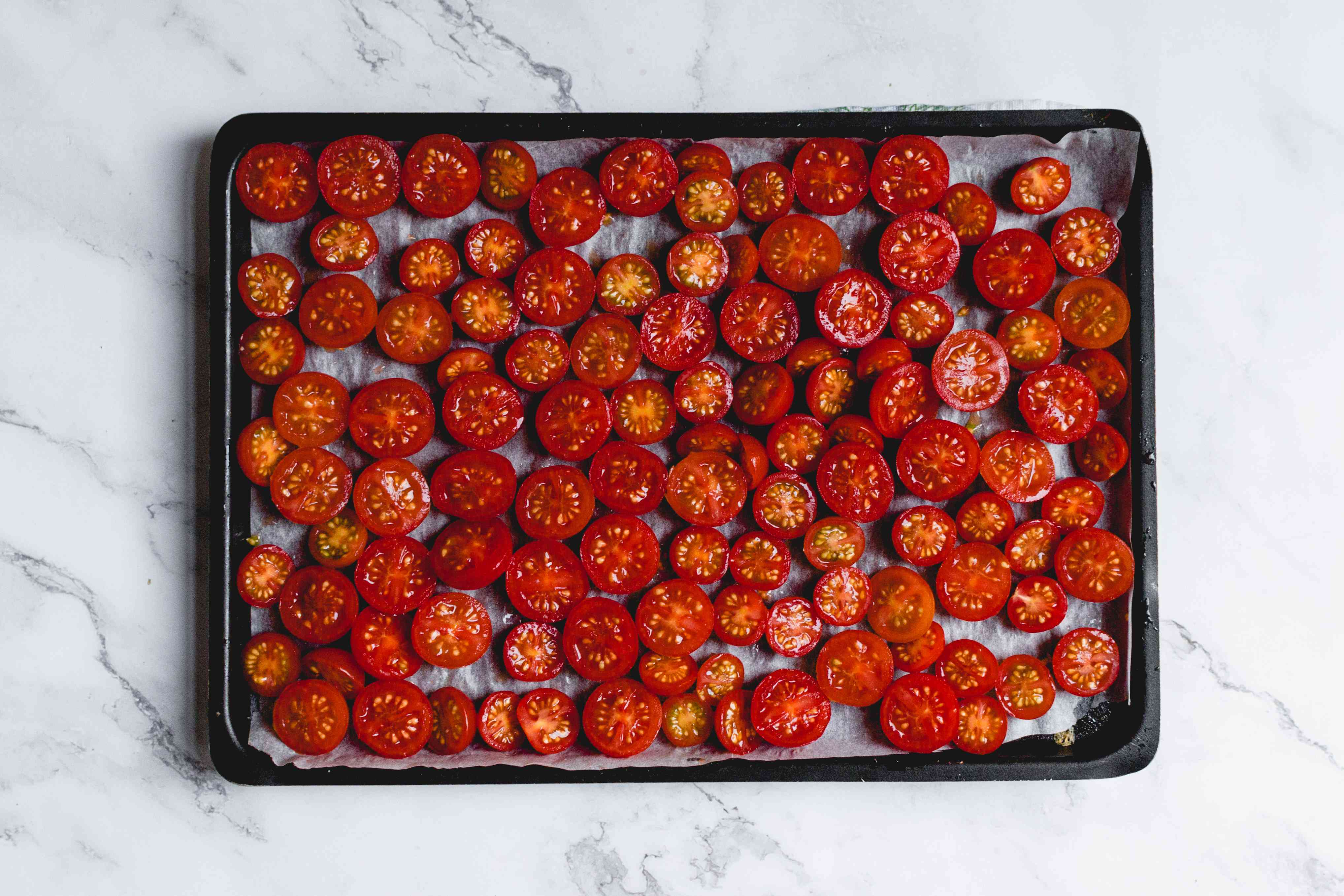 tomatoes on a parchment lined baking sheet
