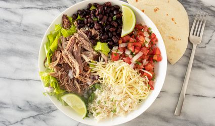 bowl of copycat carnitas with lime wedges
