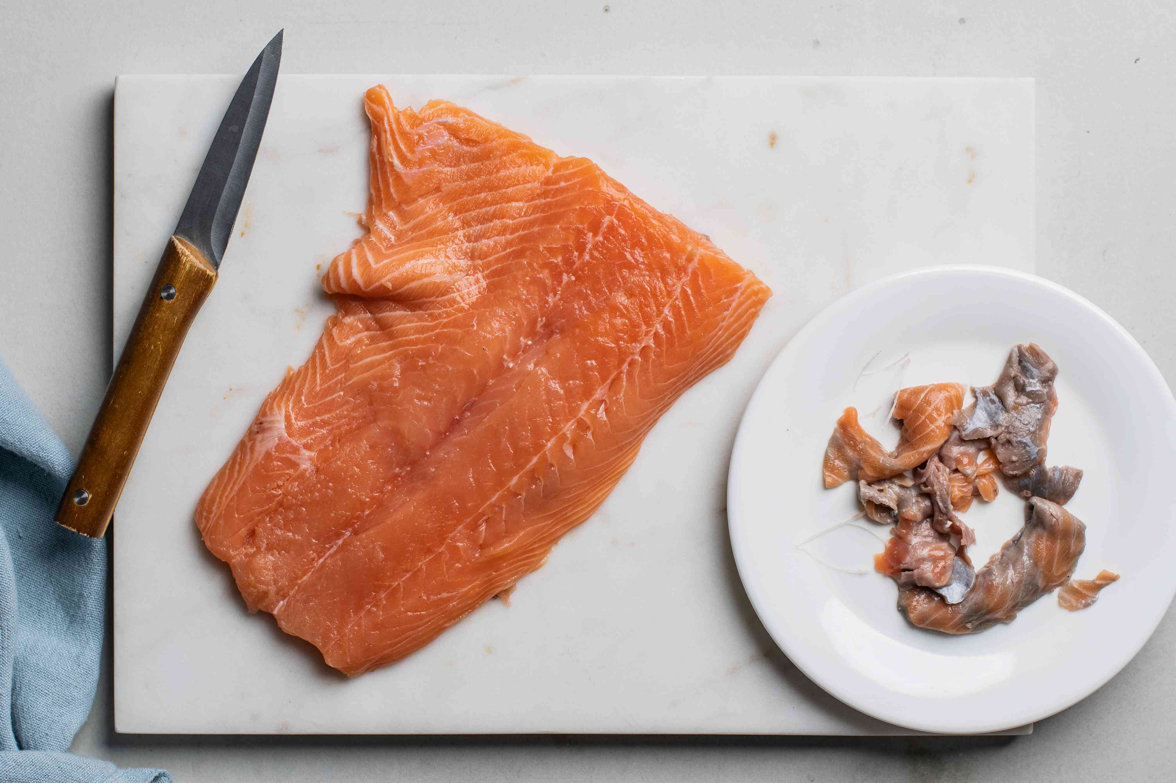Remove pin bones and dark gray bloodline from salmon