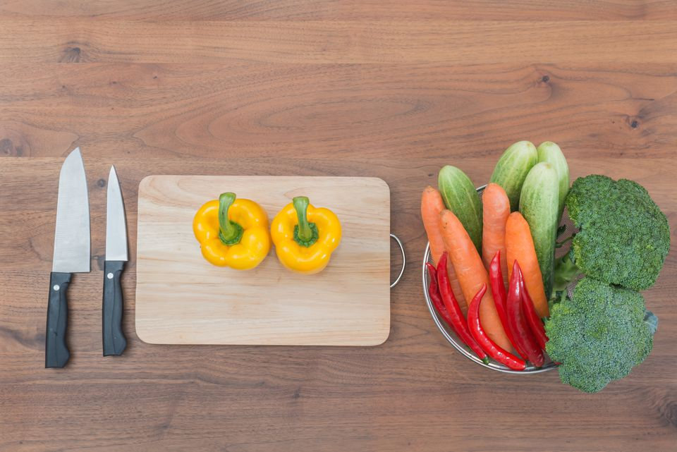 Vegetable, knife and block on wooden table in kitchen