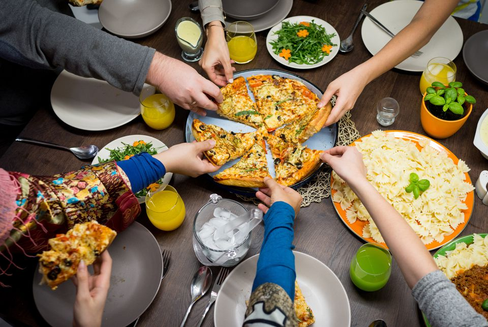 Hands all reaching in to pizza