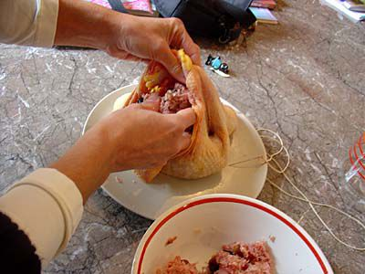 Stuff the chicken, pressing down firmly to compact the stuffing