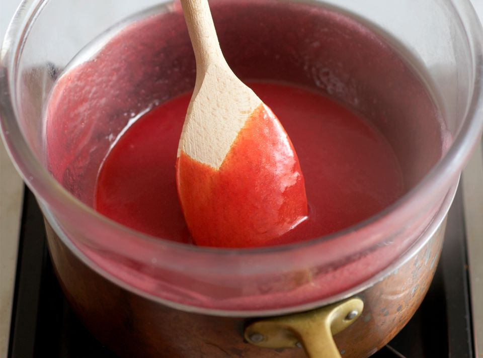 Wooden spoon stirring heated raspberry curd in a double boiler.