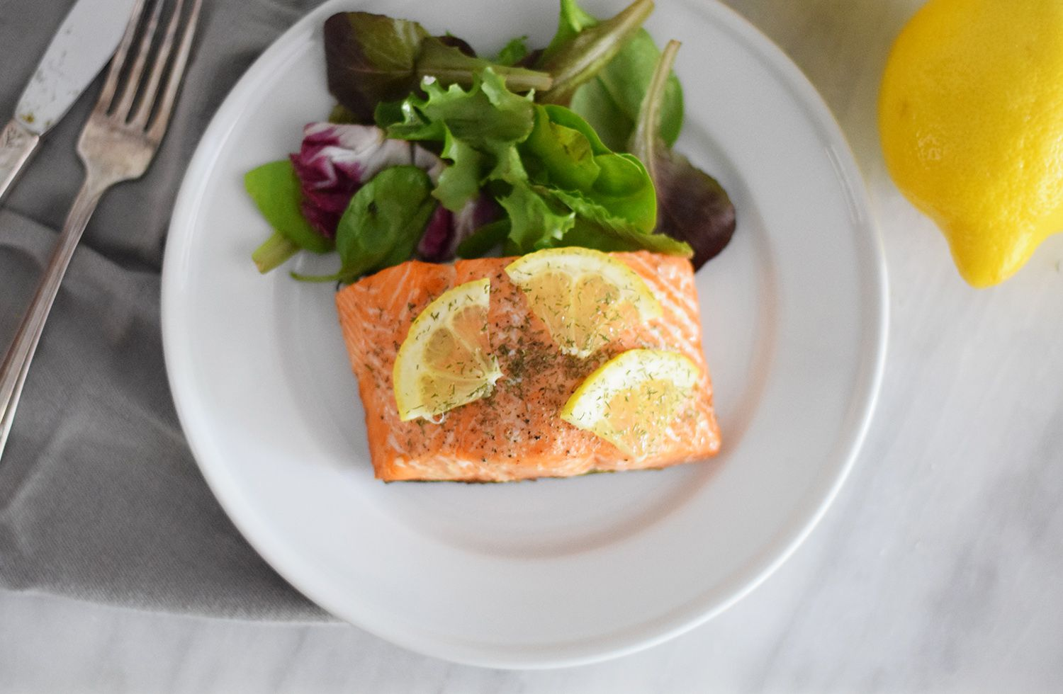 Grilled salmon topped with bits of fresh lemon and served with leafy greens
