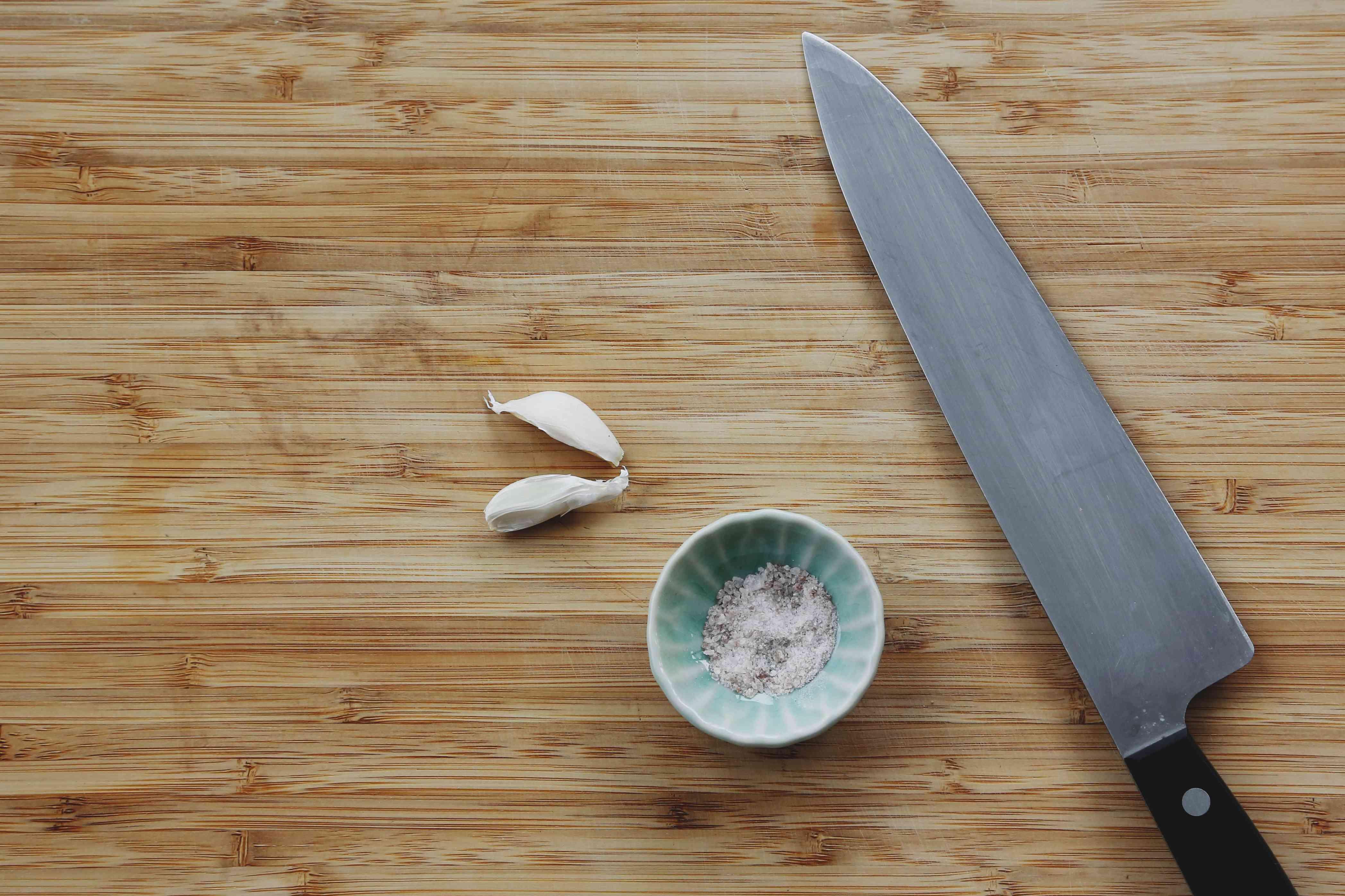 garlic on a cutting board, salt in a small bowl