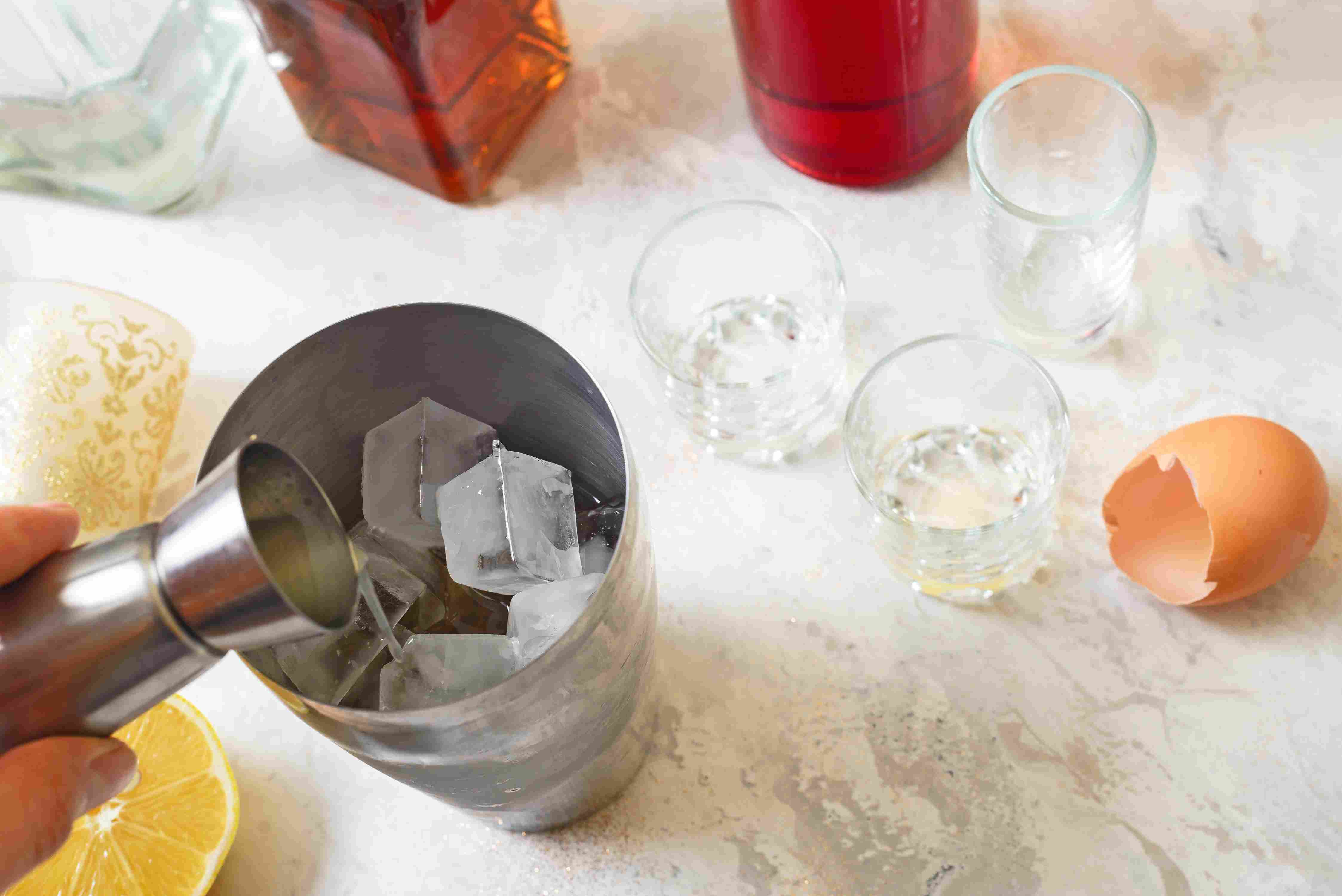 Pour ingredients into a cocktail shaker with ice cubes