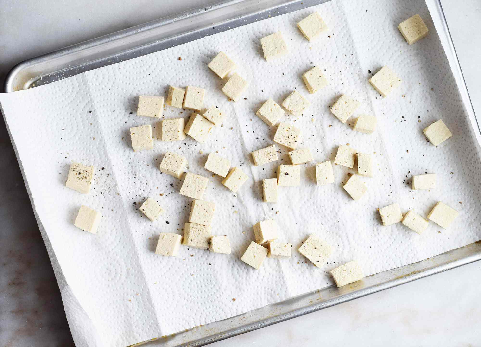 tofu on paper towels sprinkled with salt and pepper